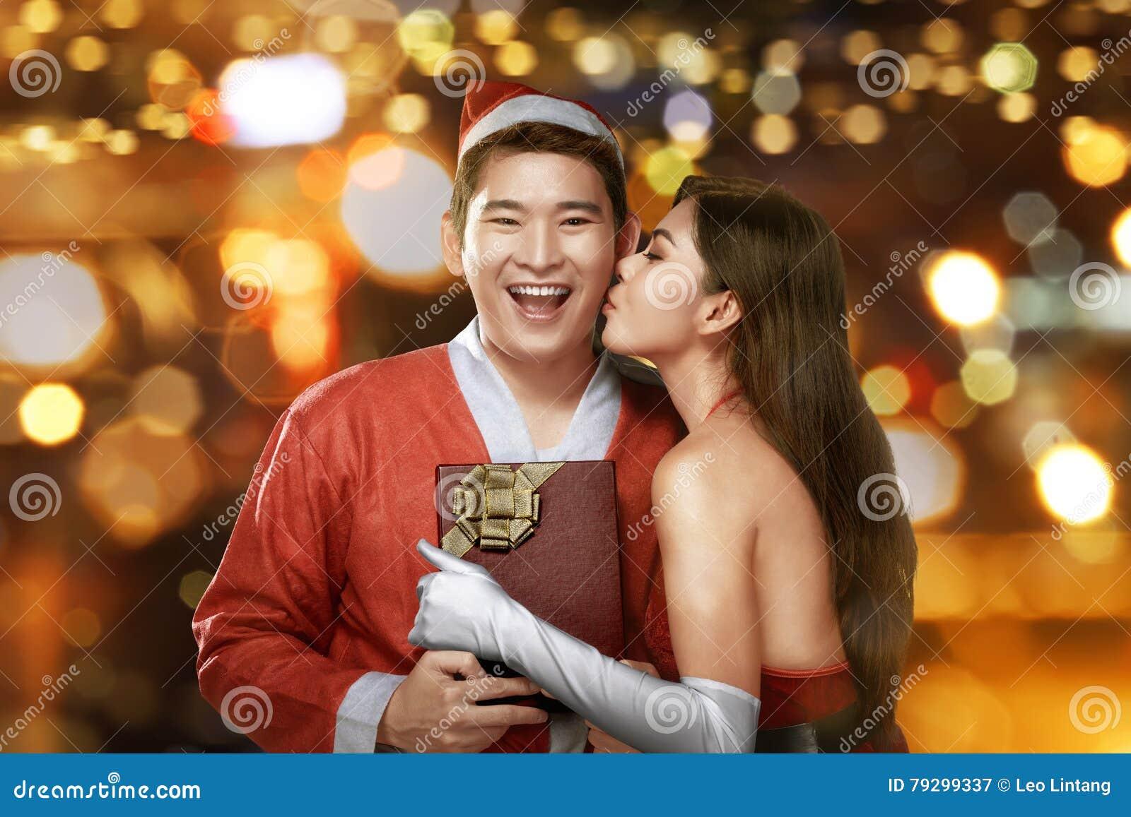 Молодая азиатская женщина целуя ее партнера на рождестве