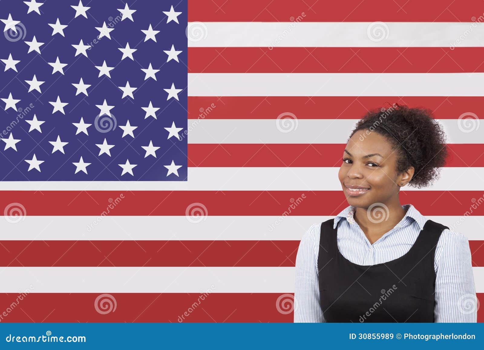 Молодая Афро-американская коммерсантка усмехаясь над американским флагом