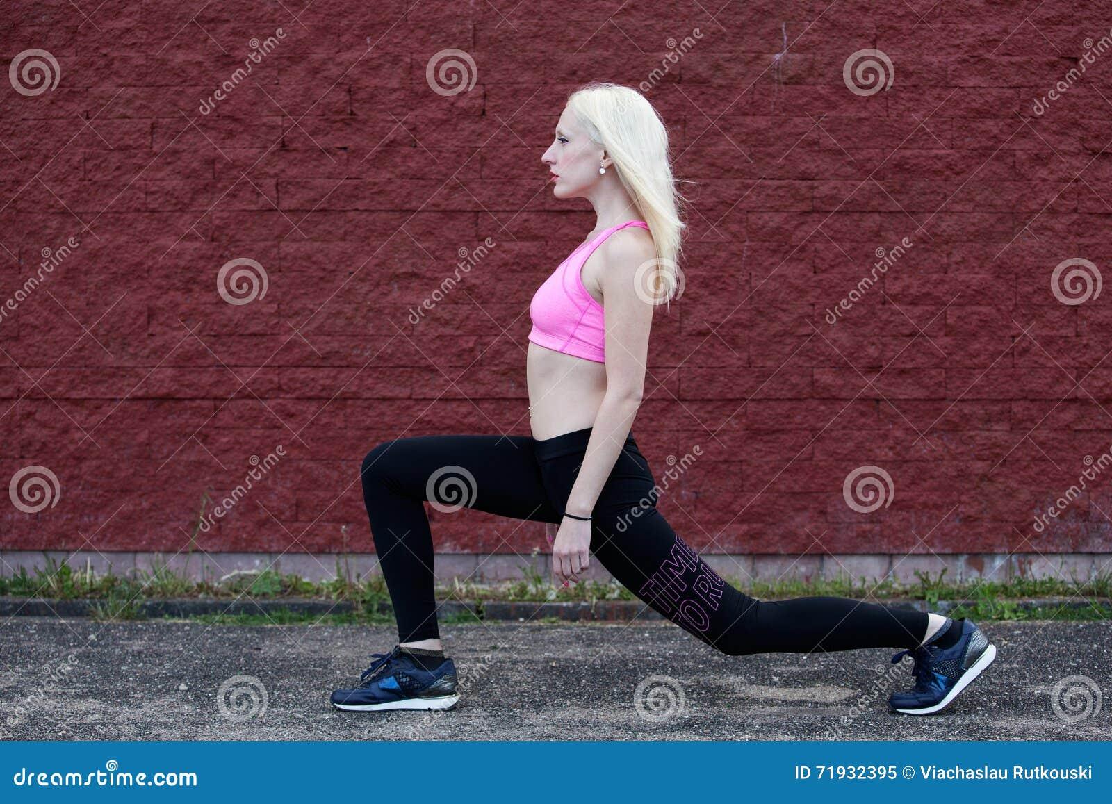Молодая белокурая женщина делает сидение на корточках outdoors