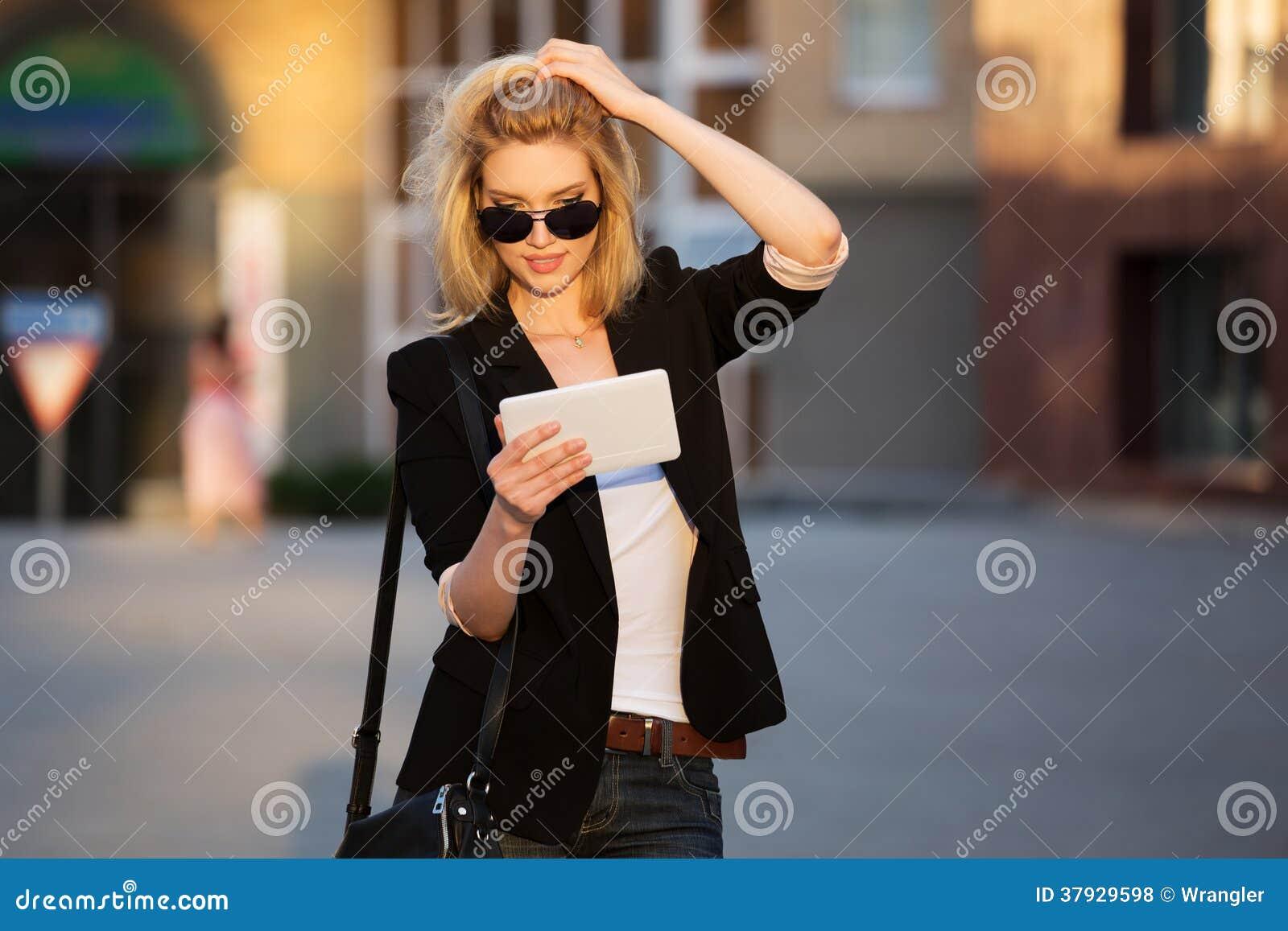Молодая бизнес-леди используя цифровой планшет
