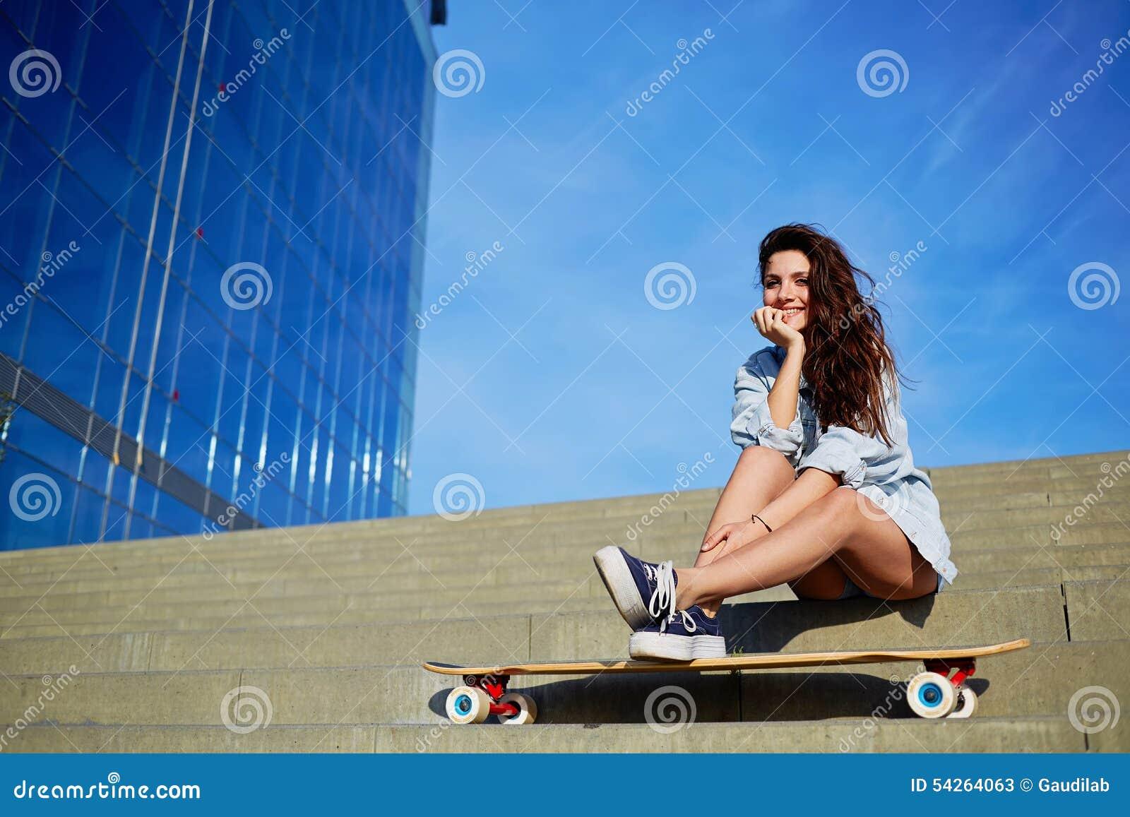 Молодая девушка битника представляя на смотреть красивого захода солнца светлый прочь