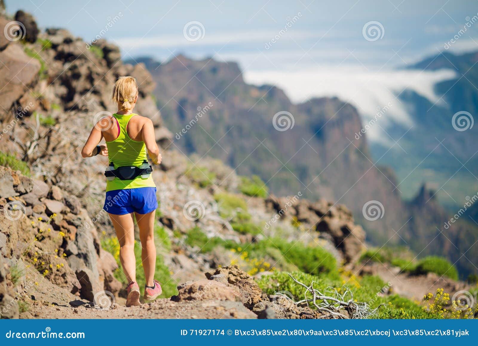 Молодая женщина бежать в горах на летний день