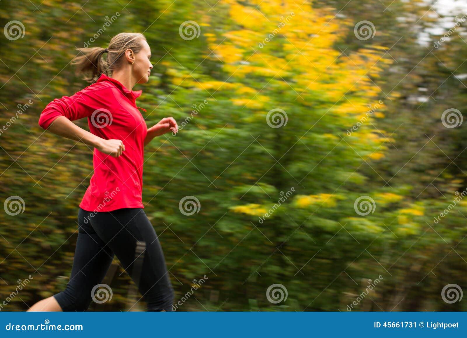 Молодая женщина бежать outdoors в парке города