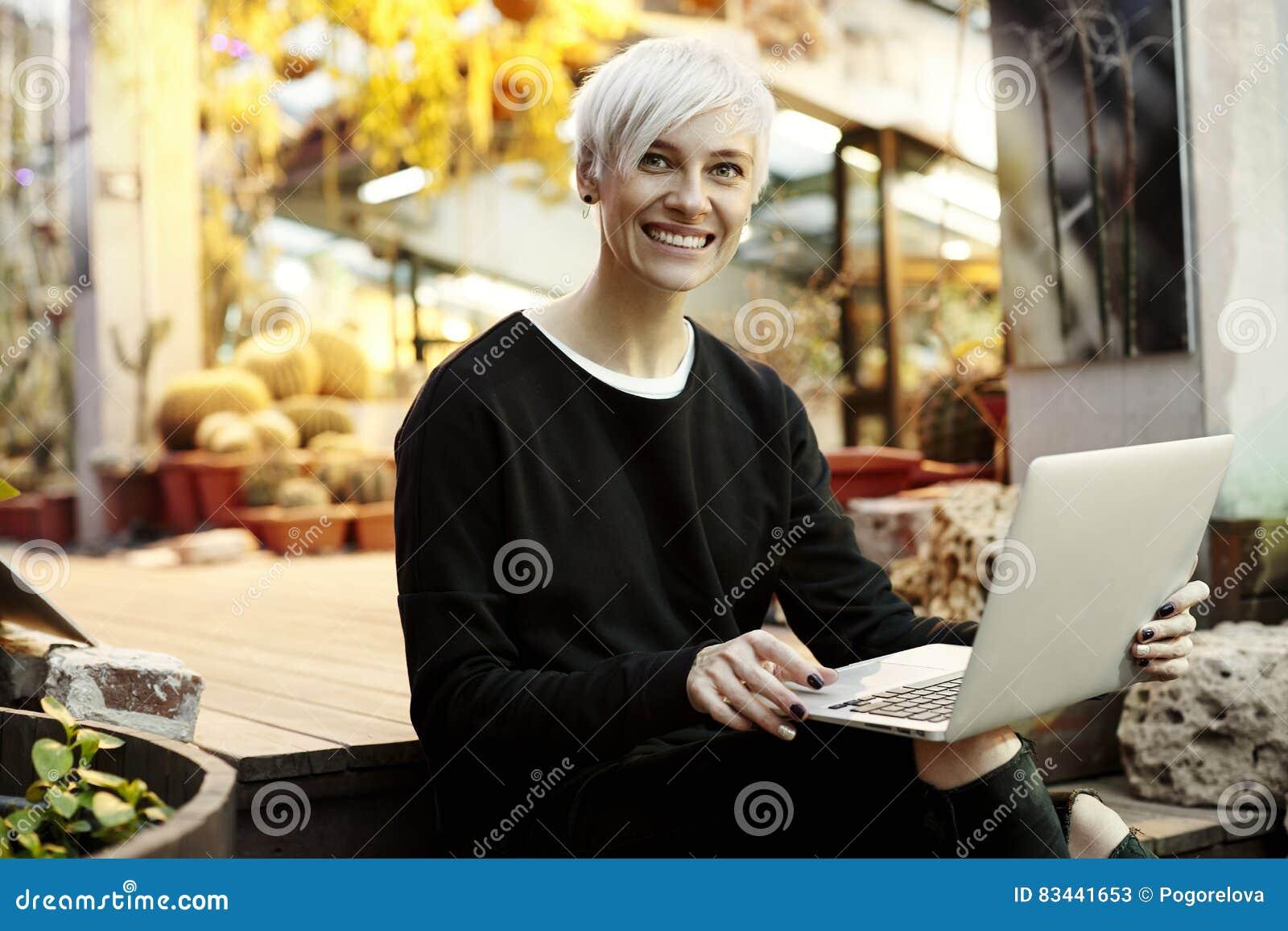 Молодая женщина битника с белокурыми короткими волосами усмехаясь и работая на компьтер-книжке, сидя на лестницах Крытый интерьер