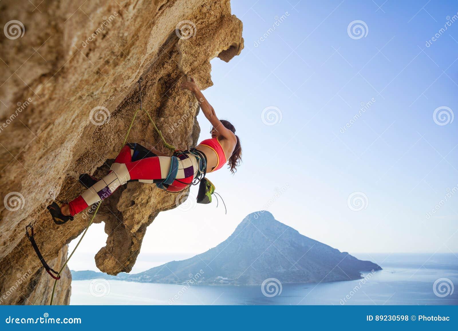 Молодая женщина борясь для того чтобы взобраться свисая скала