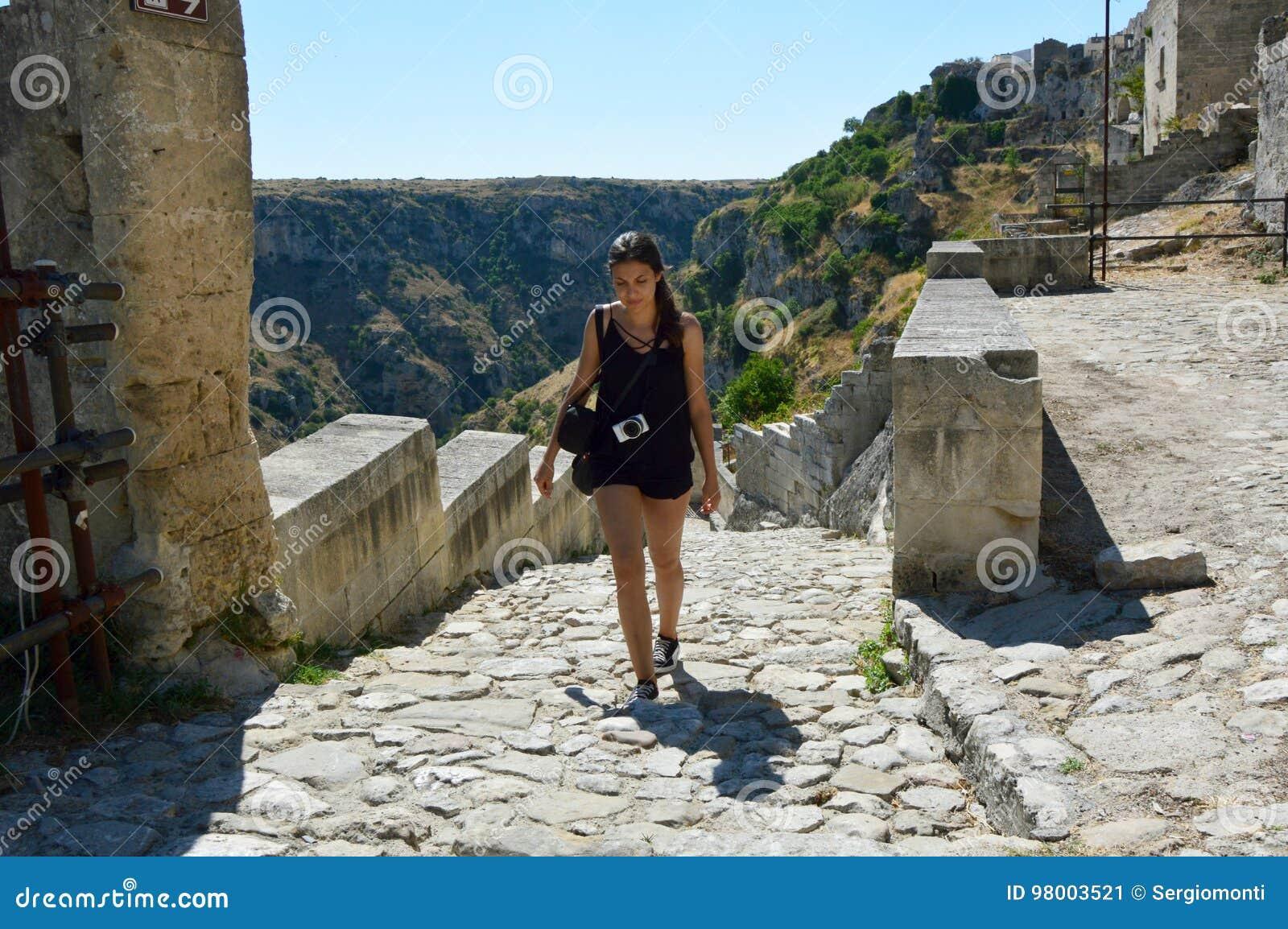 Молодая женщина взбираясь полет шагов в старый городок места Matera, всемирного наследия ЮНЕСКО и европейской столицы культуры 20