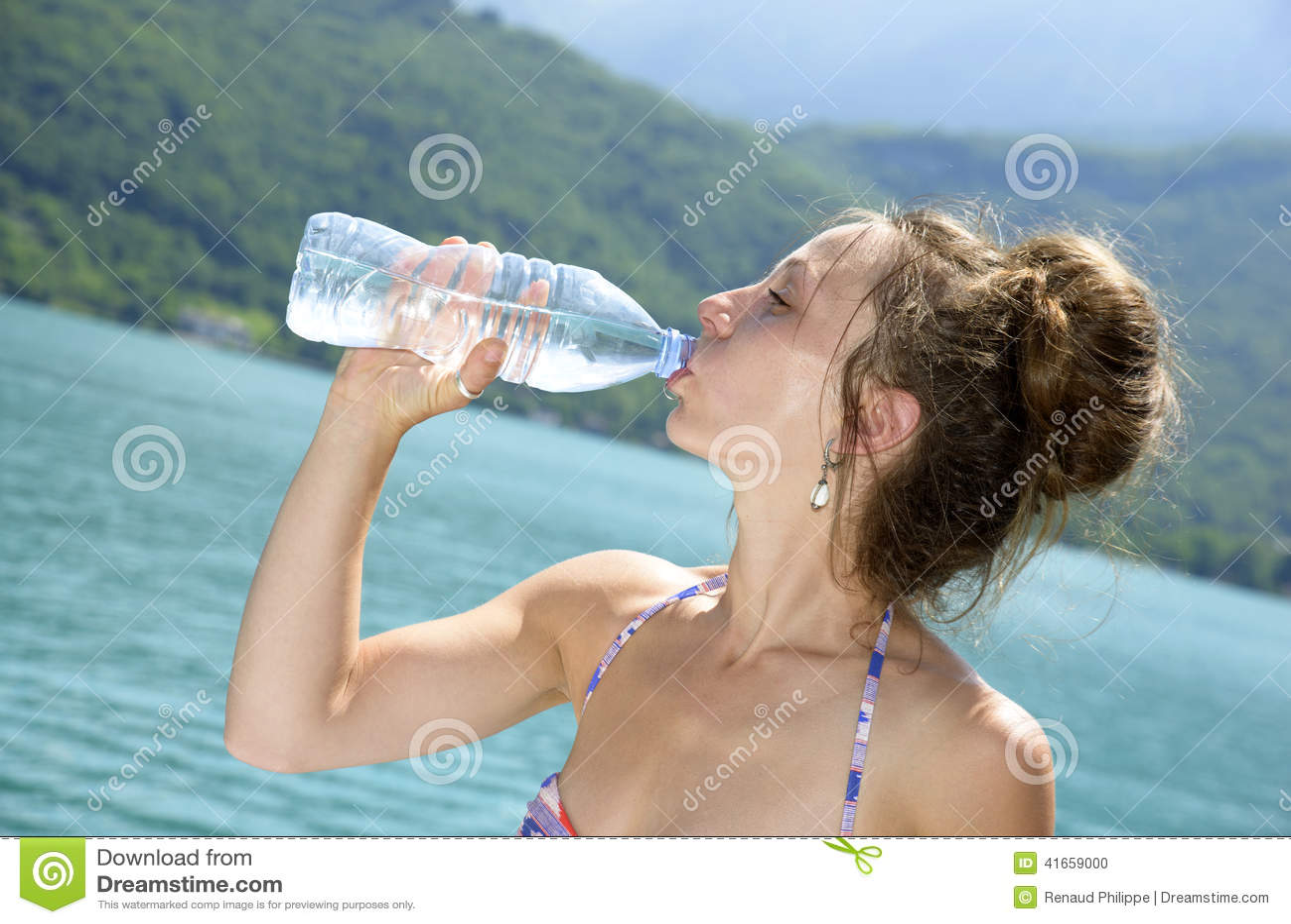 Молодая женщина выпивает бутылку воды к пляжу