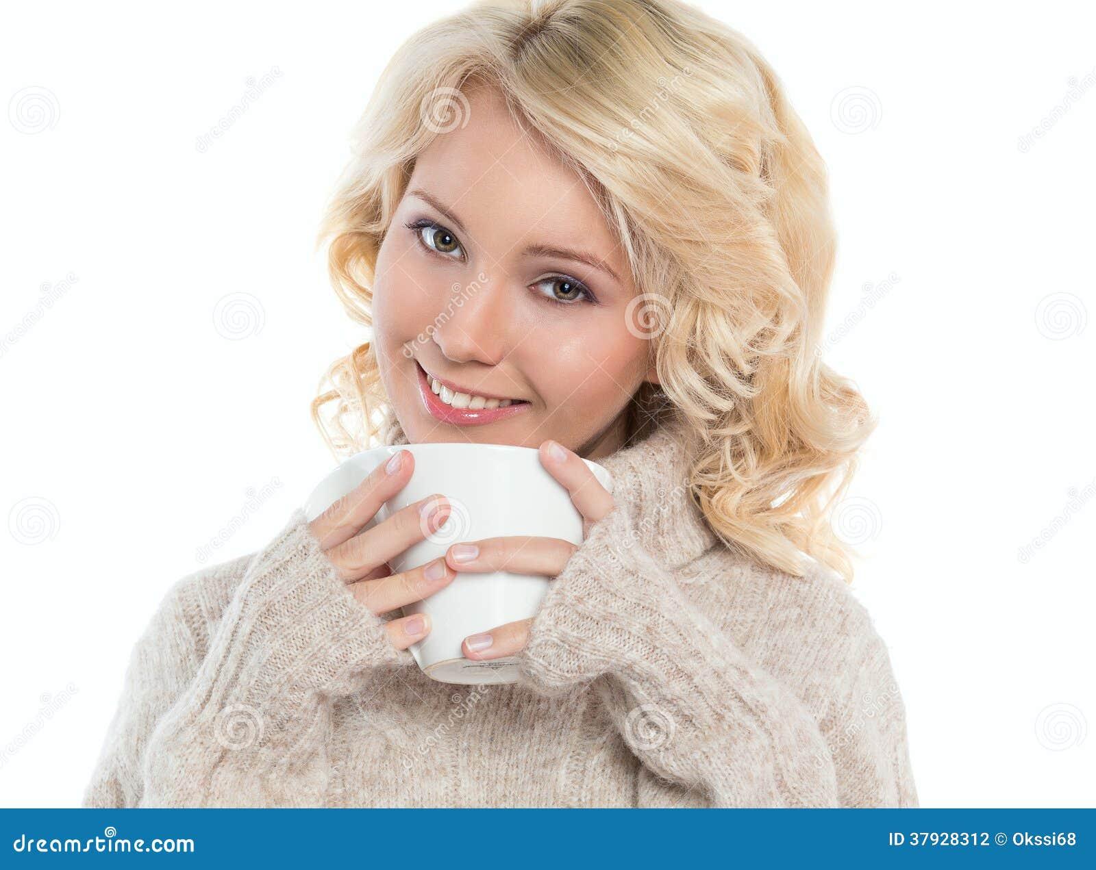 Молодая женщина в теплом свитере и кружке в его руках