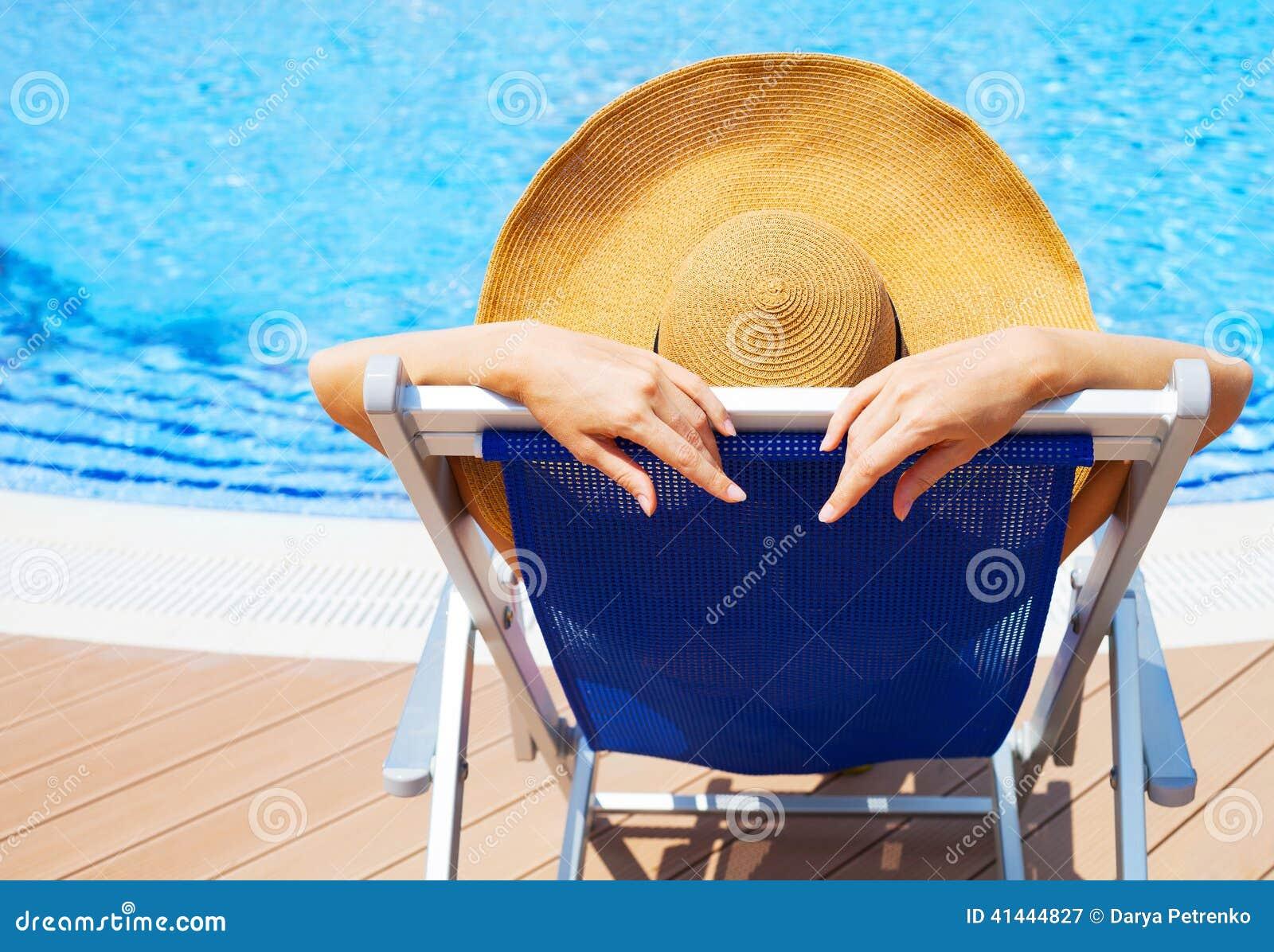 Молодая женщина лежа на deckchair бассейном