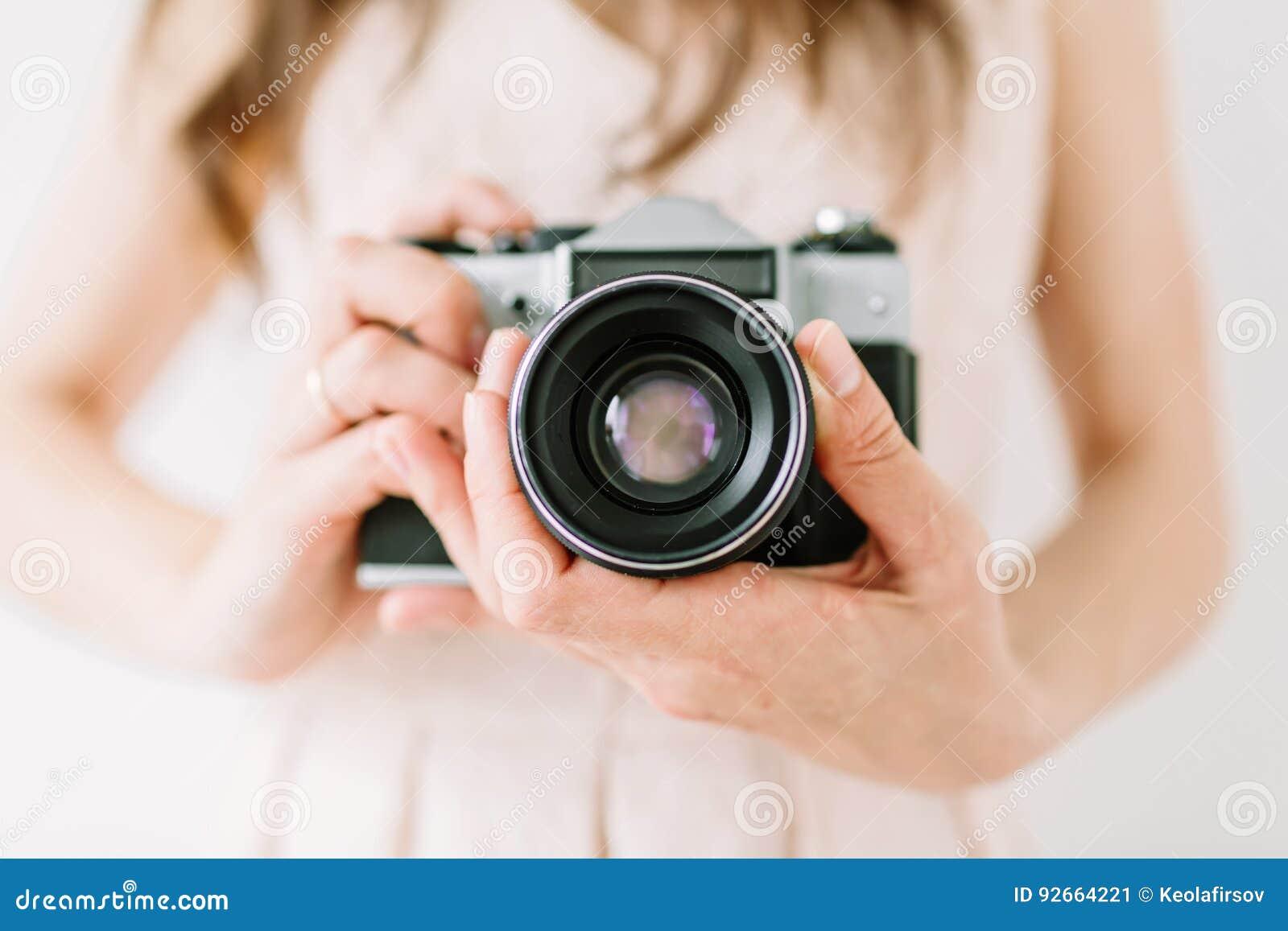 Молодая женщина держа в камере рук старой винтажной Камера фотографа и фильма девушки