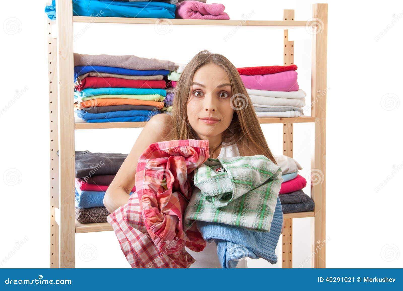Молодая женщина держа кучу одежд