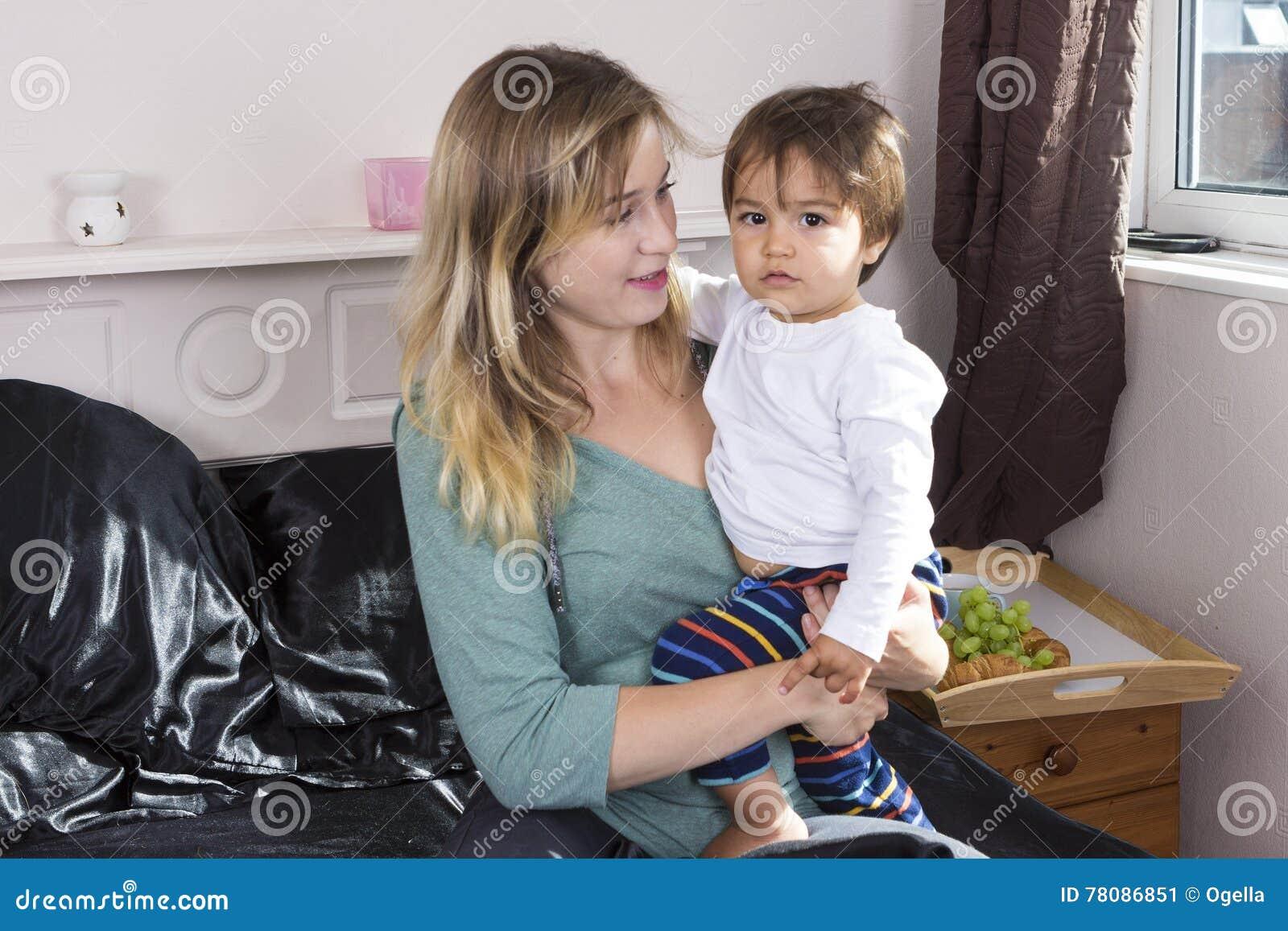 Молодая женщина держа сына на оружиях