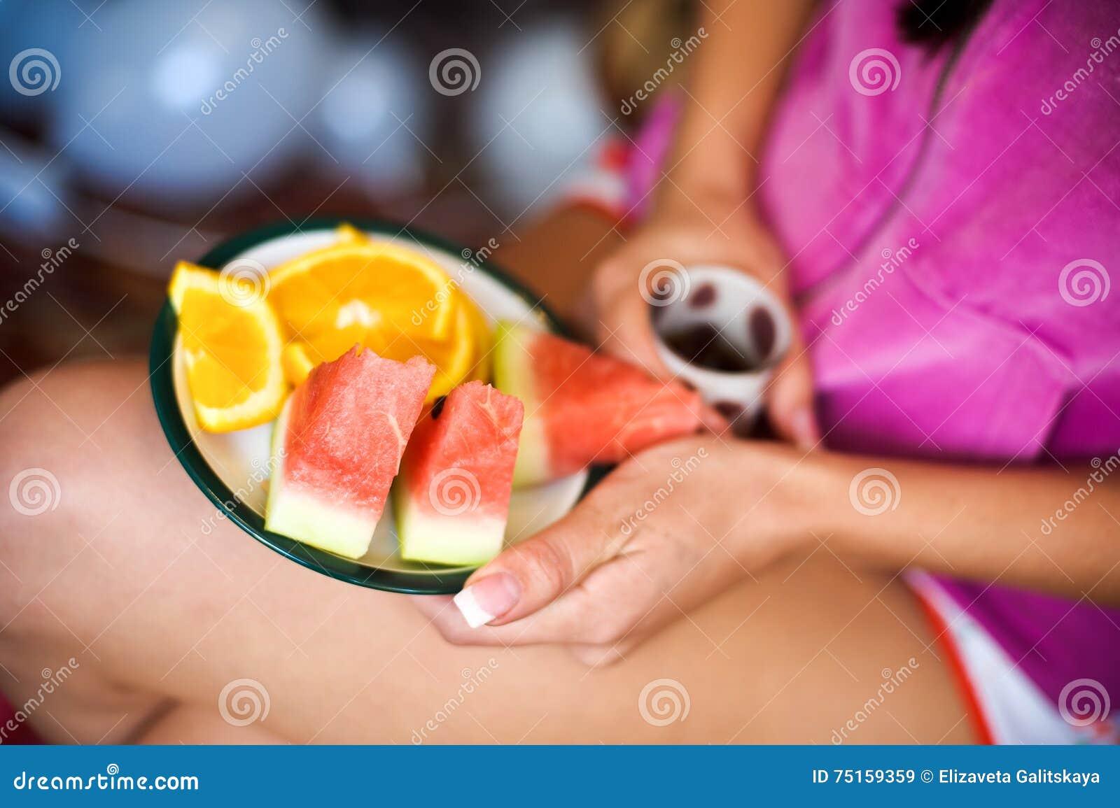 Молодая женщина держит плиту с арбузами и апельсинами