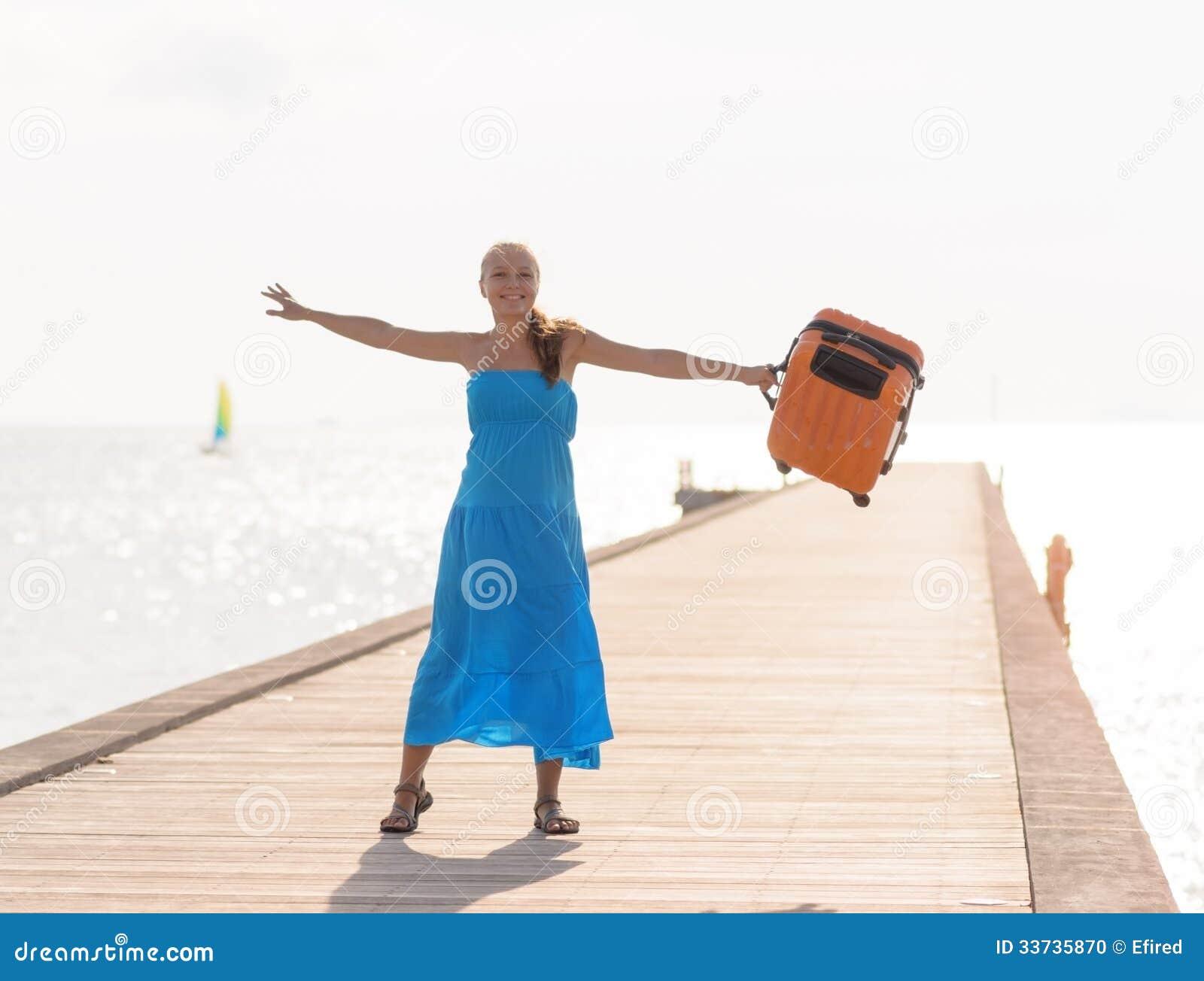 Молодая женщина имея потеху на деревянной пристани