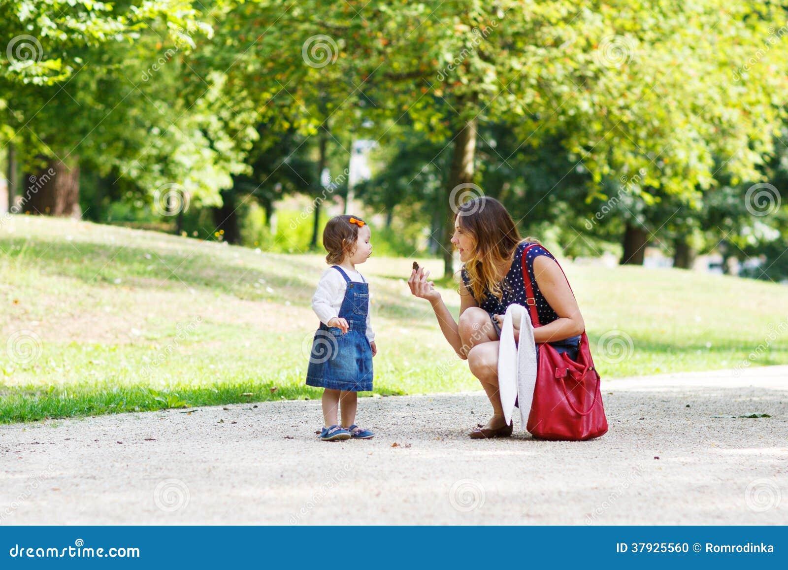Молодая женщина и маленькая девочка одного года идя до лето p