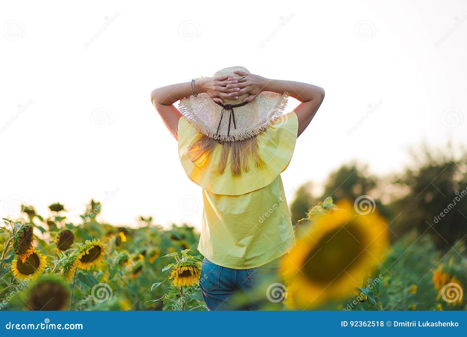 Молодая женщина моды с солнцем цветет и в шортах стильной шляпы и голубых джинсов