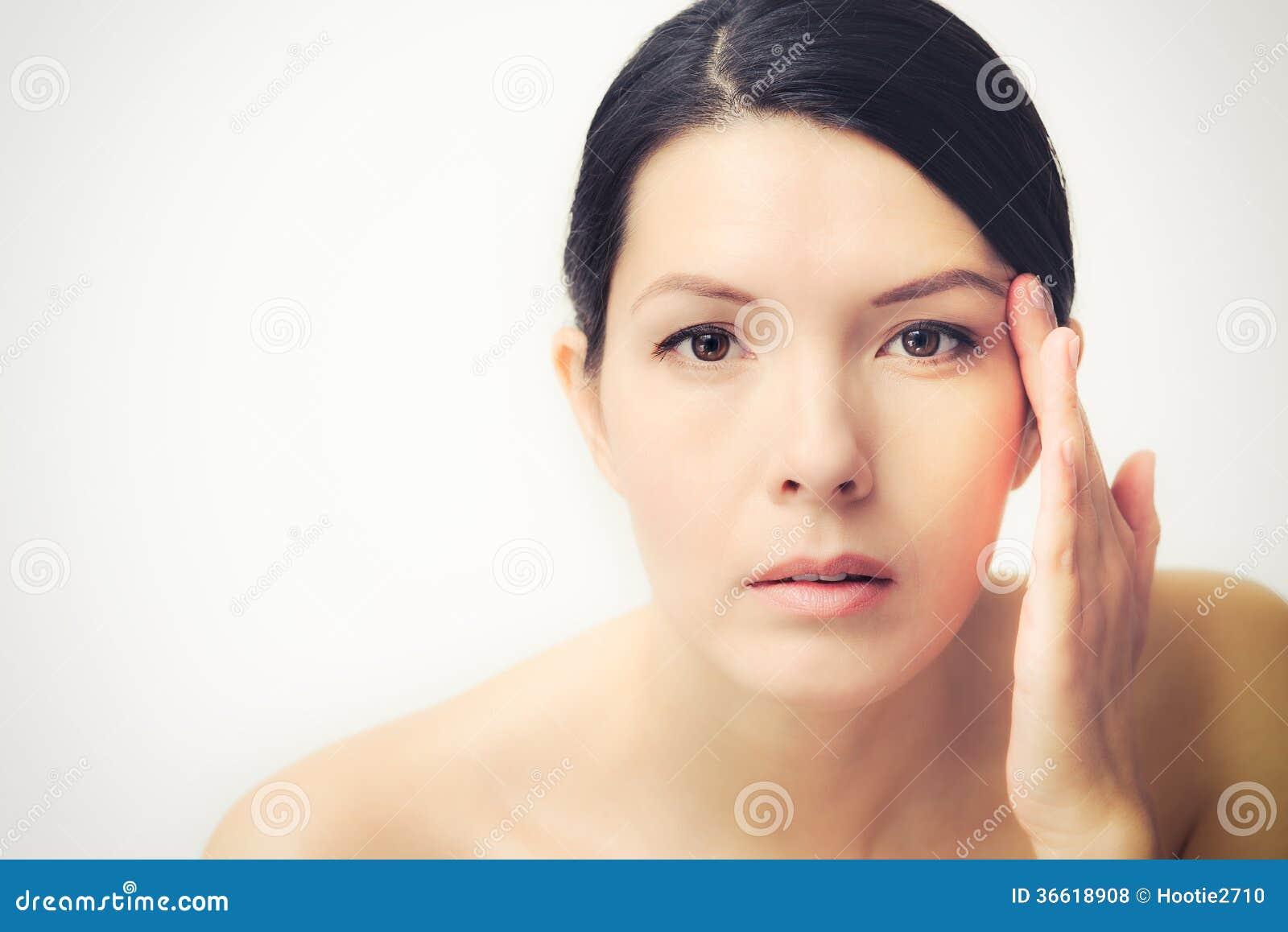 Молодая женщина наблюдающ лицевыми морщинками