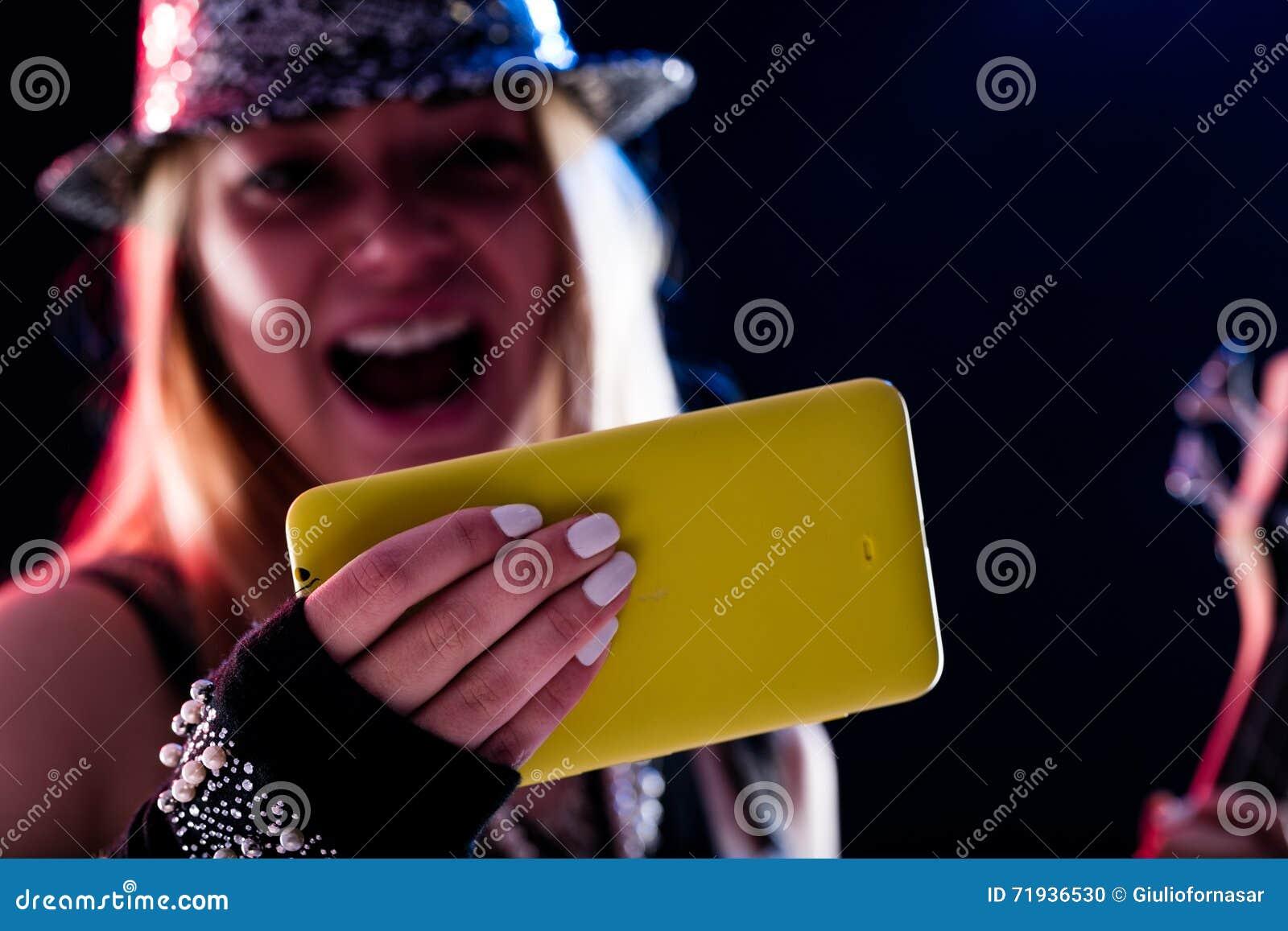 Молодая женщина наслаждаясь живым развлечением онлайн