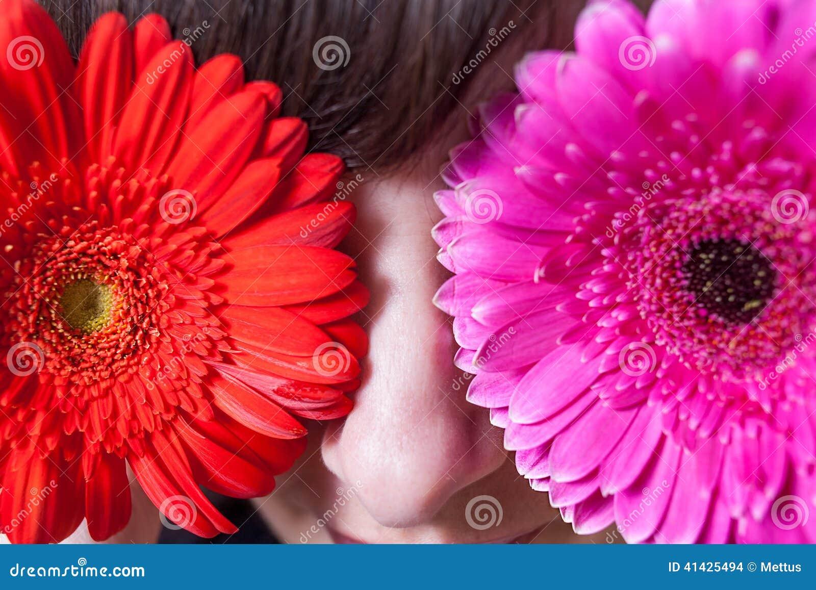 Молодая женщина покрывая ее глаза с свежими красочными цветками Макрос