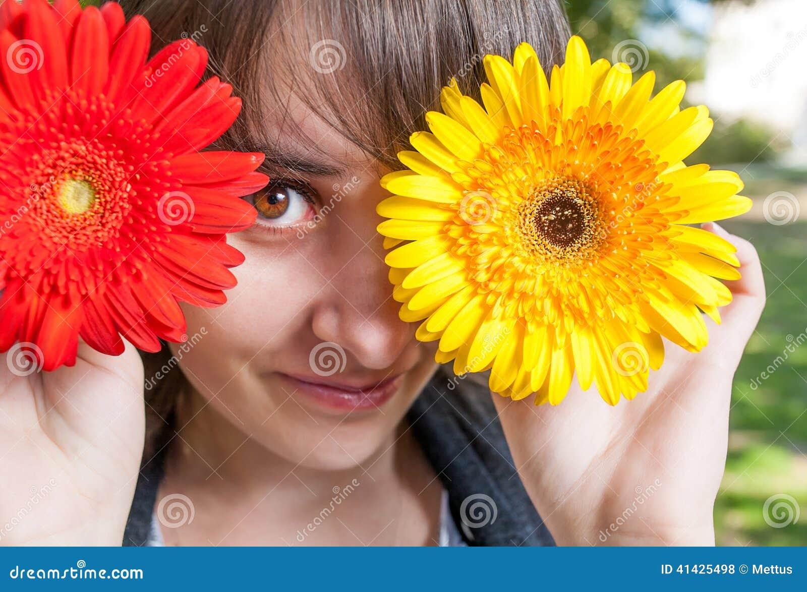 Молодая женщина покрывая ее глаза с свежими красочными цветками насладитесь
