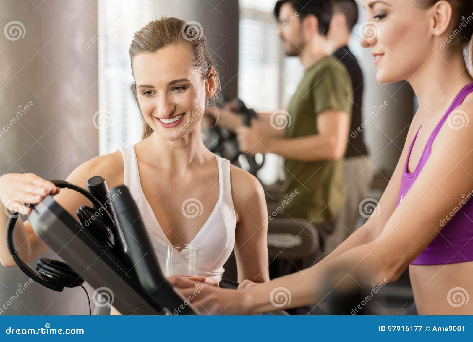 Молодая женщина помогая ее другу установить время, скорость и inclin