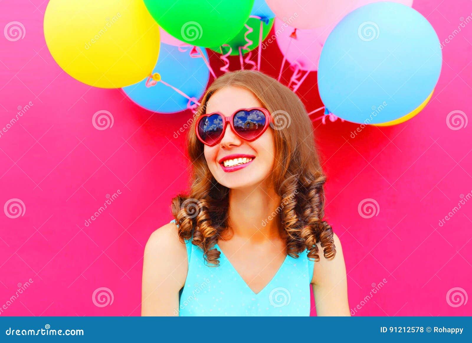 Молодая женщина портрета счастливая усмехаясь имея потеху над пинком воздушных шаров воздуха красочным