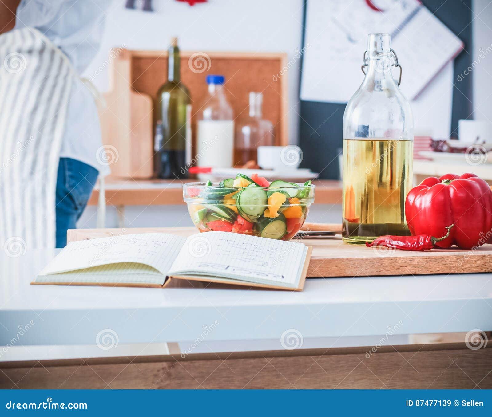Молодая женщина подготавливая салат в кухне