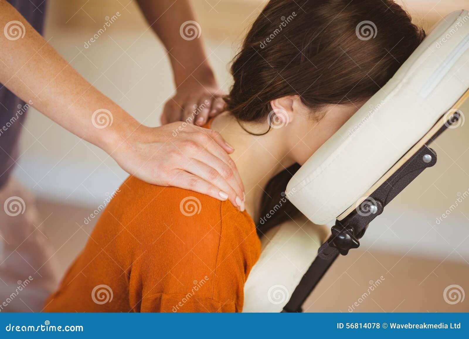 Молодая женщина получая массаж в стуле