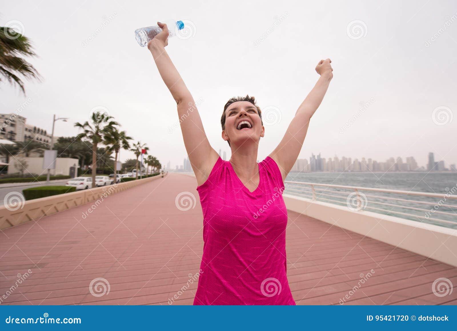 Молодая женщина празднуя успешный бег тренировки
