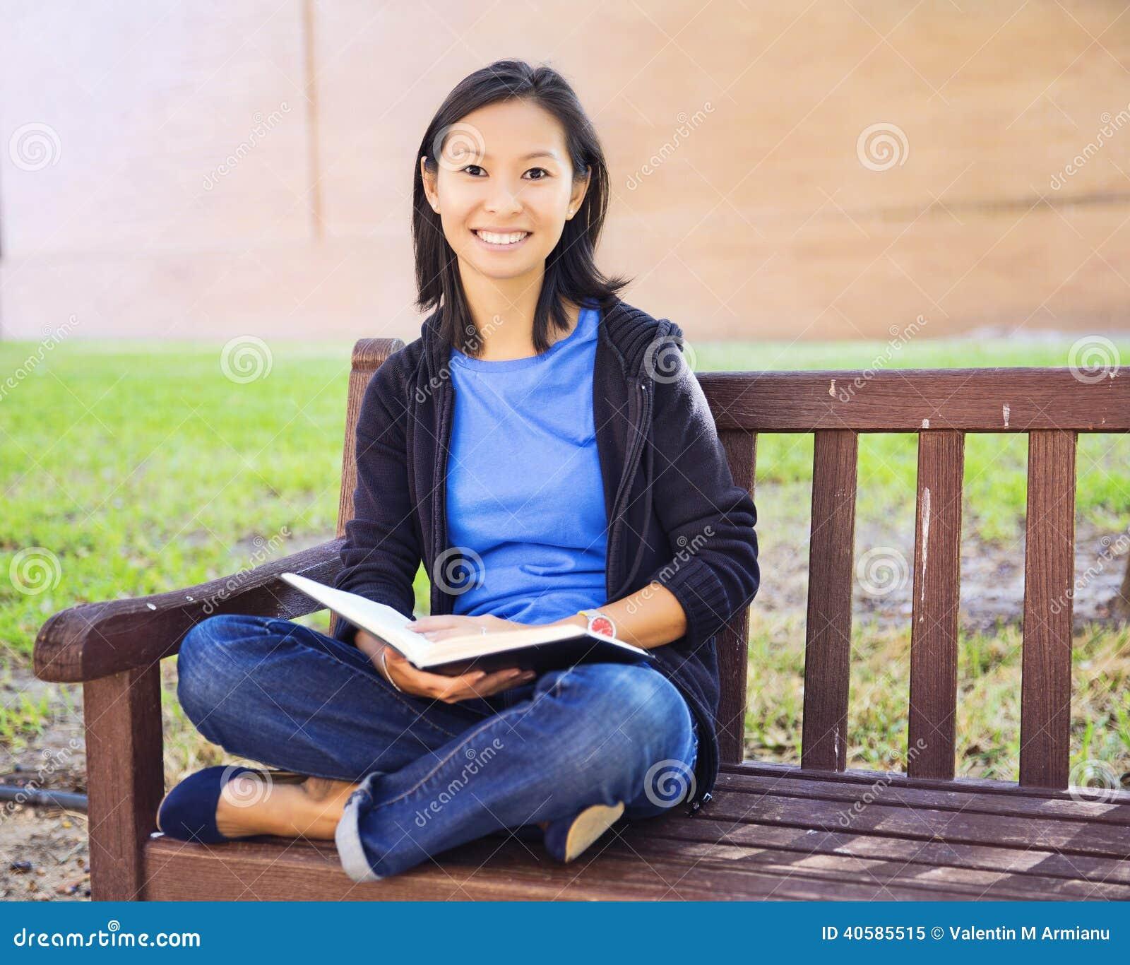 Молодая женщина при длинние волосы сидя в чтении сиденья у окна