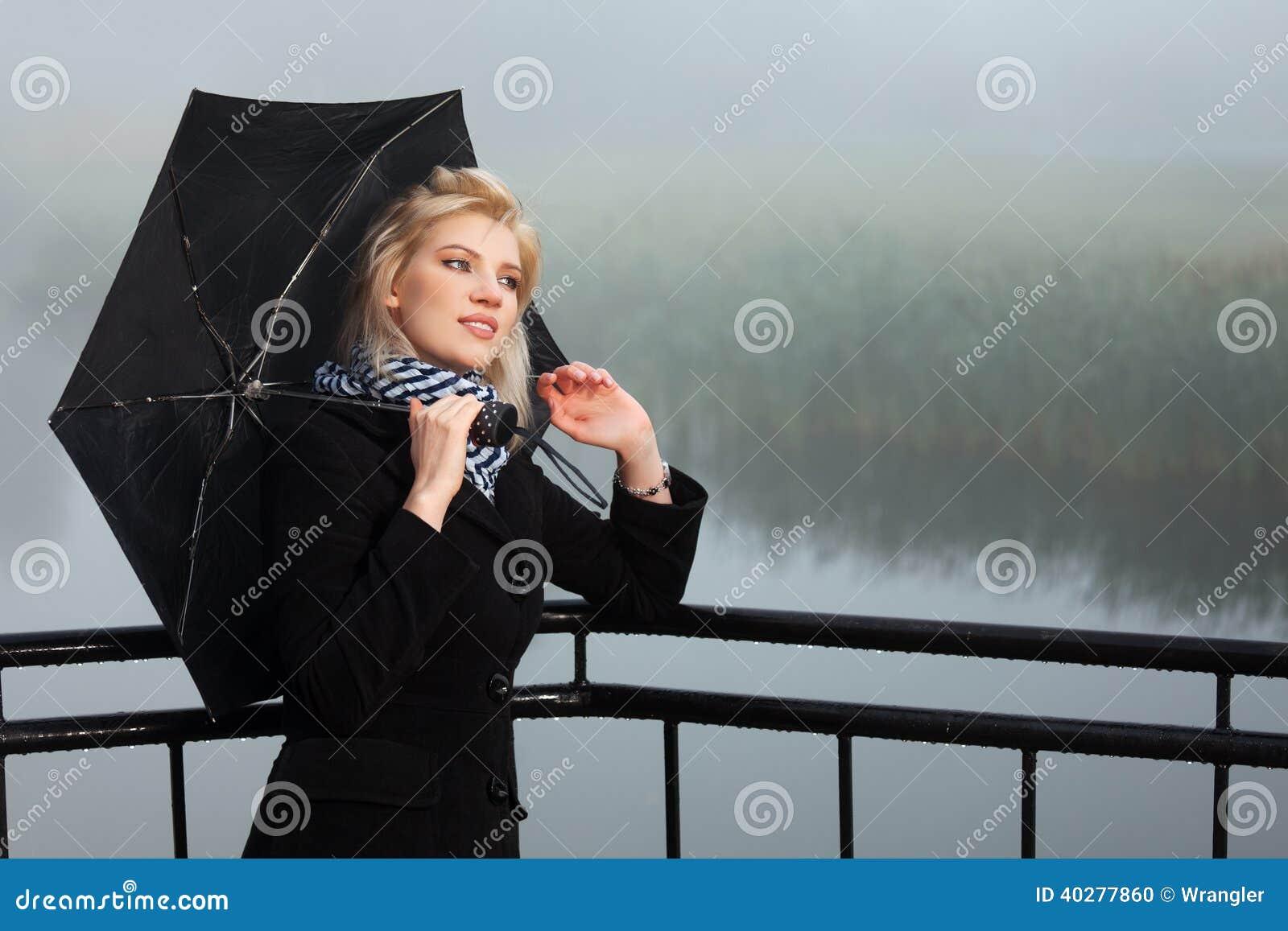 Молодая женщина против ландшафта утра туманного