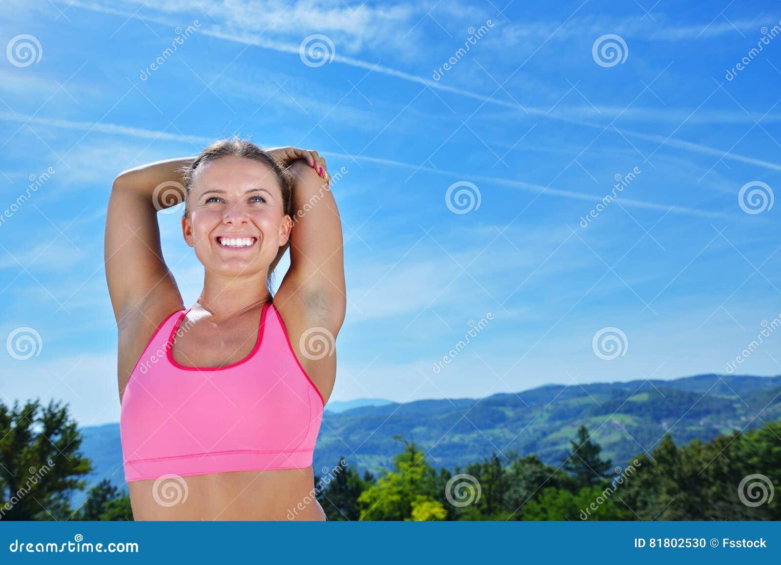 Молодая женщина протягивая ее оружия вверх пока работающ на горе