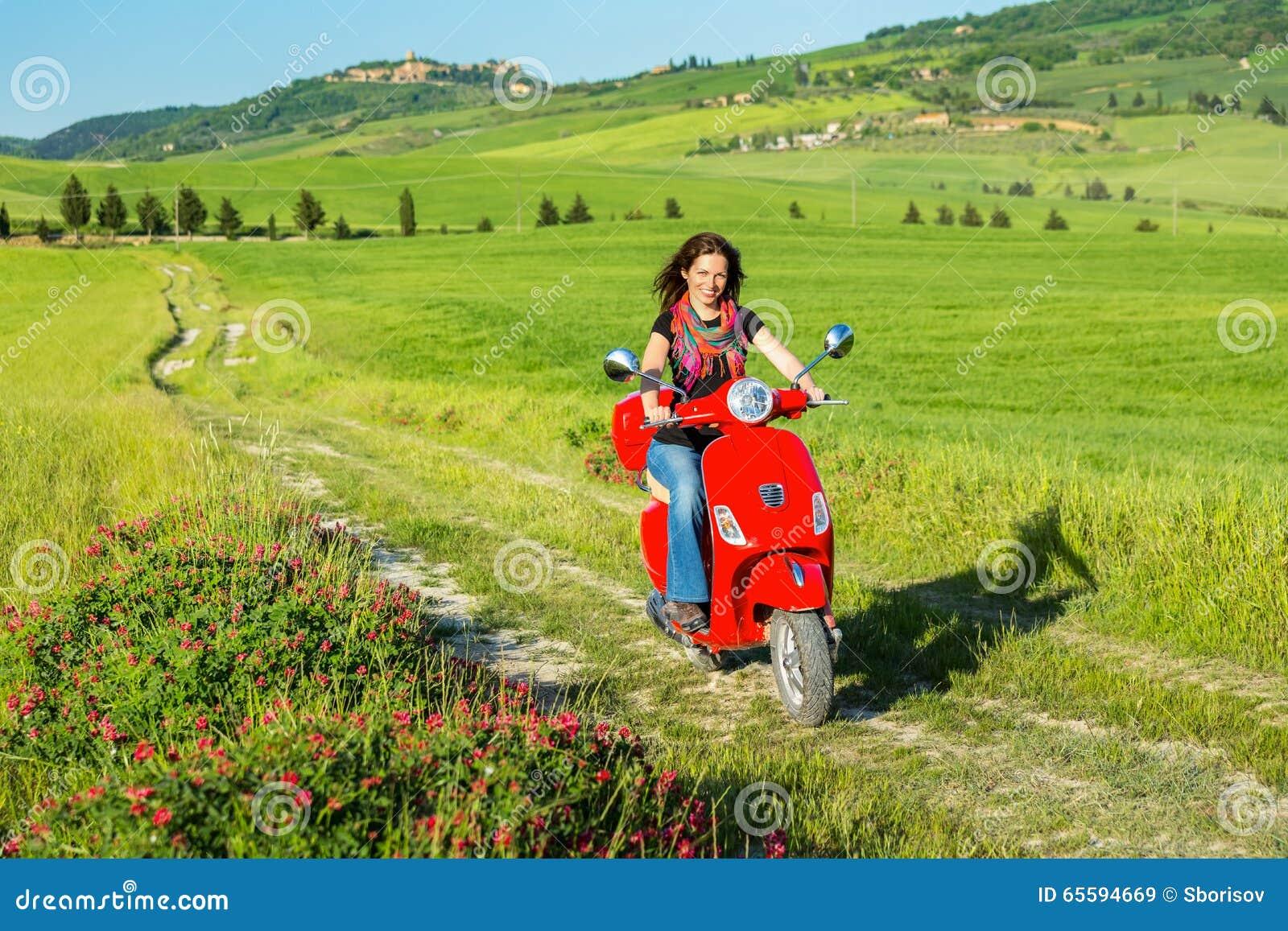 Молодая женщина путешествуя самокатом
