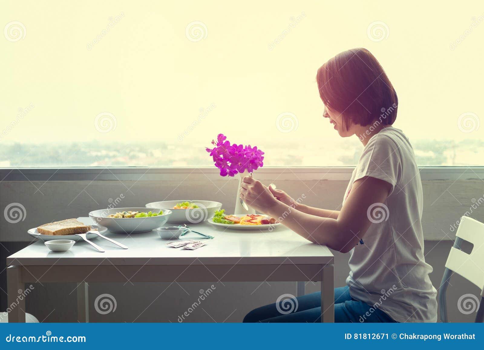 Молодая женщина сидя на комнате на таблице и есть обедающий самостоятельно