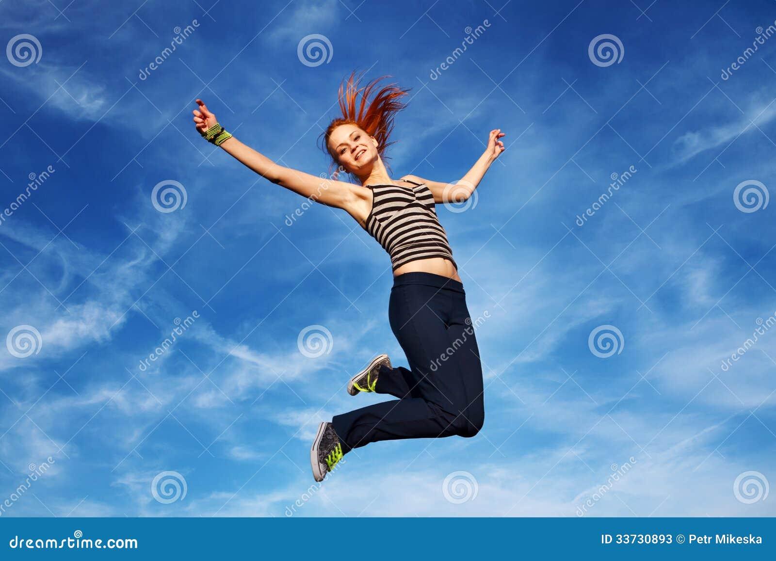 Молодая женщина скача дальше под открытым небом