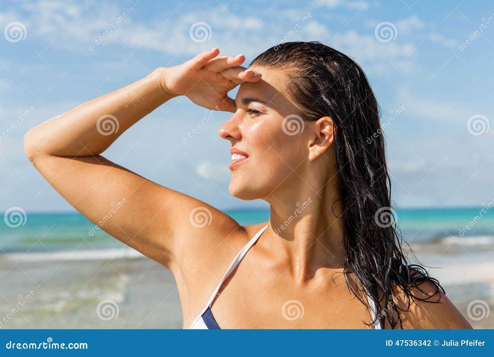 Молодая женщина смотря далеко в пляже