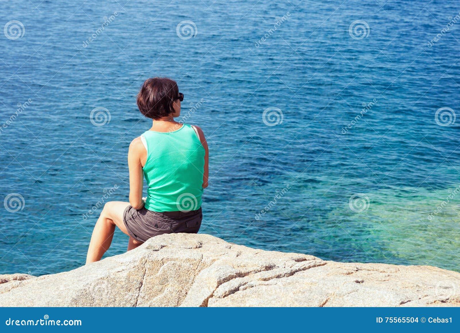 Молодая женщина смотря на море