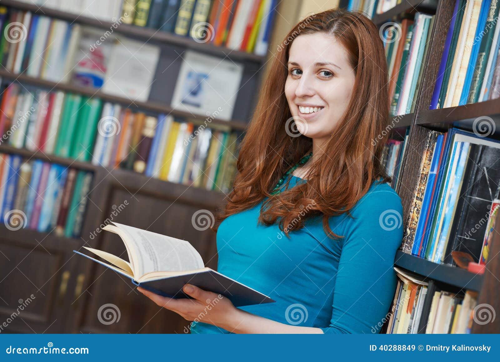 Молодая женщина с книгой в библиотеке
