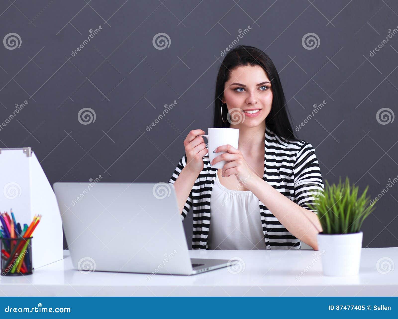 Молодая женщина с усаживанием компьтер-книжки изолированная на серой предпосылке