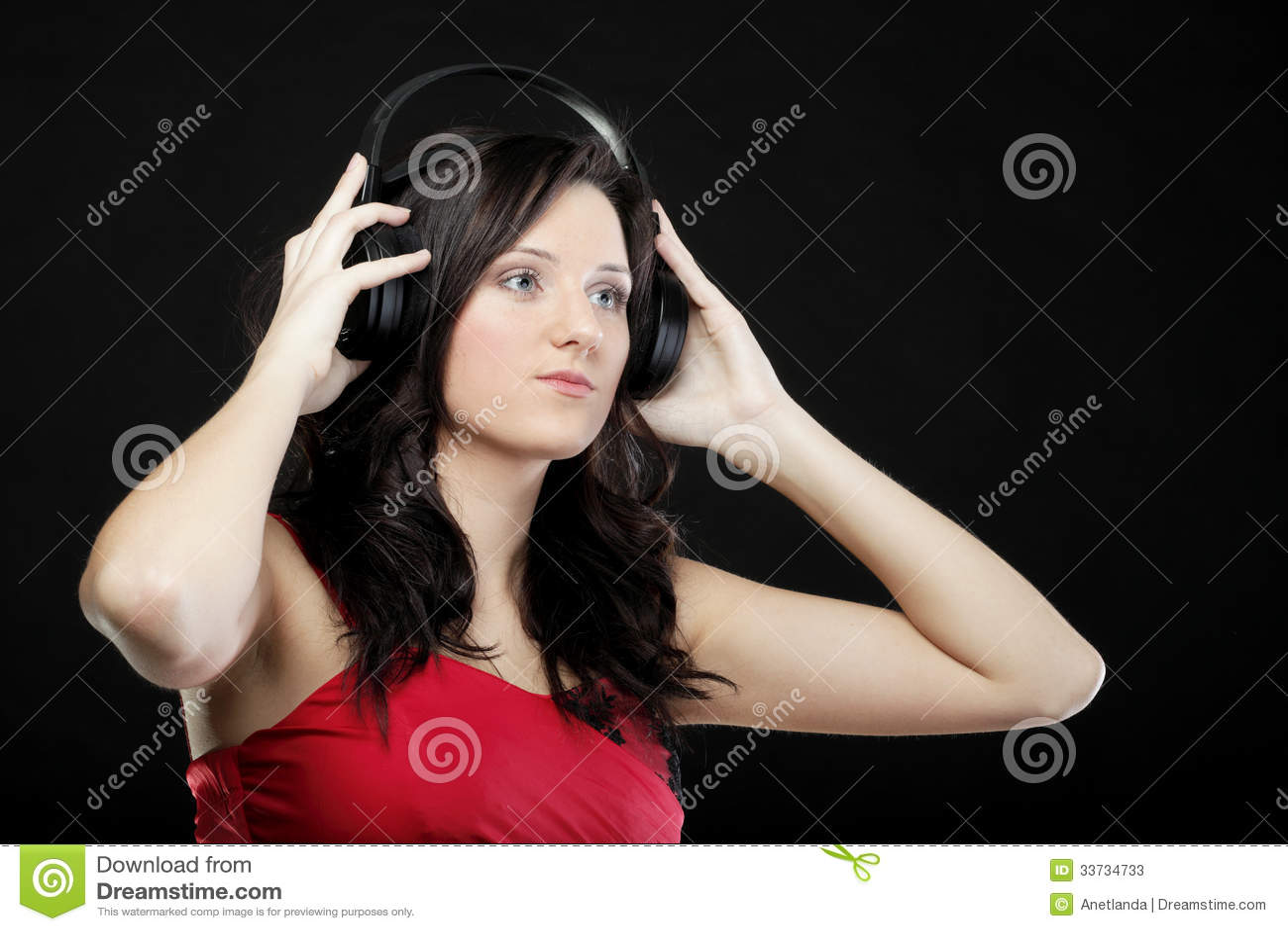 Молодая женщина слушая к музыке на шлемофоне