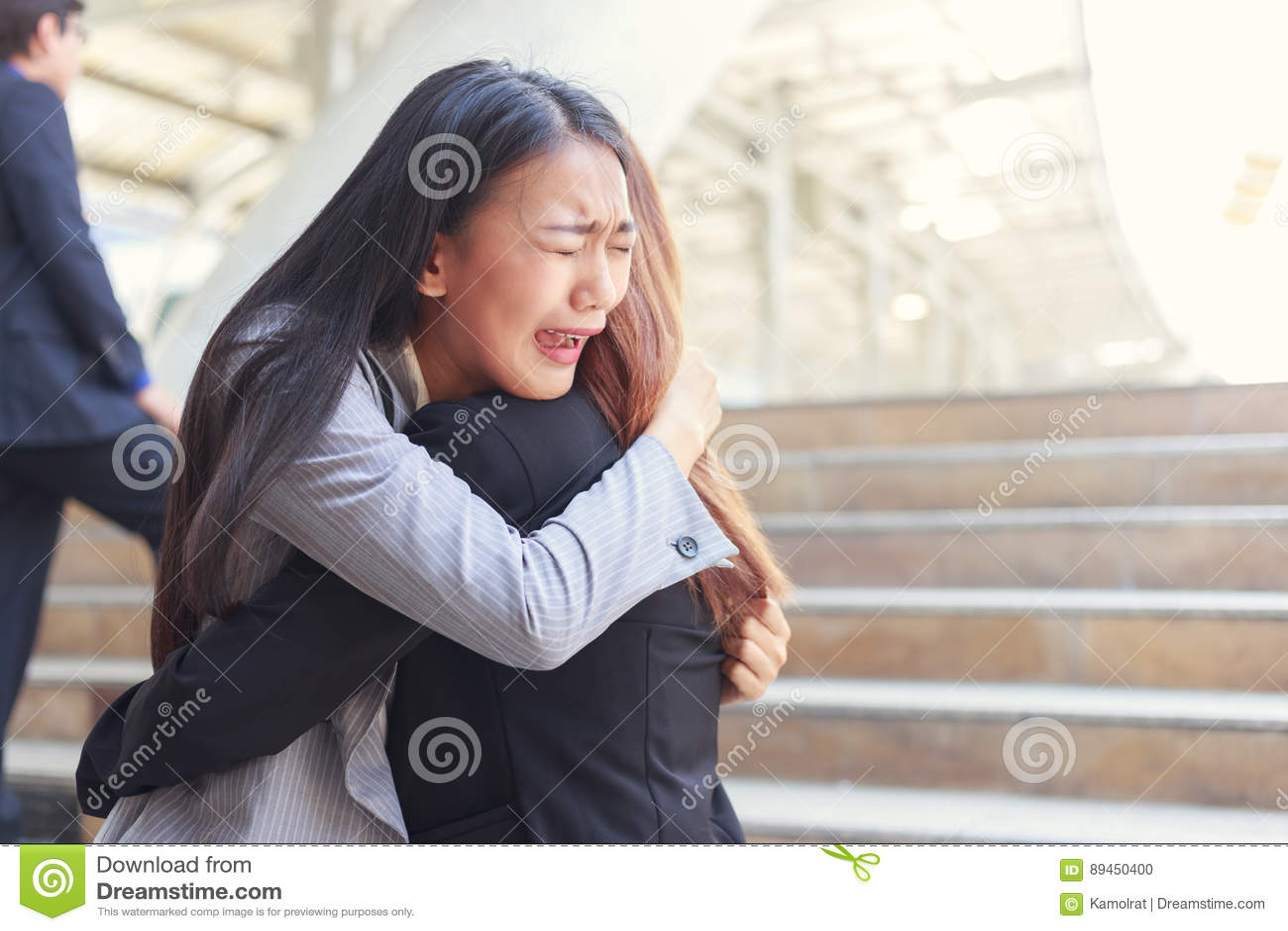 Молодая женщина унылая и плача обнимающ ее подавленного друга