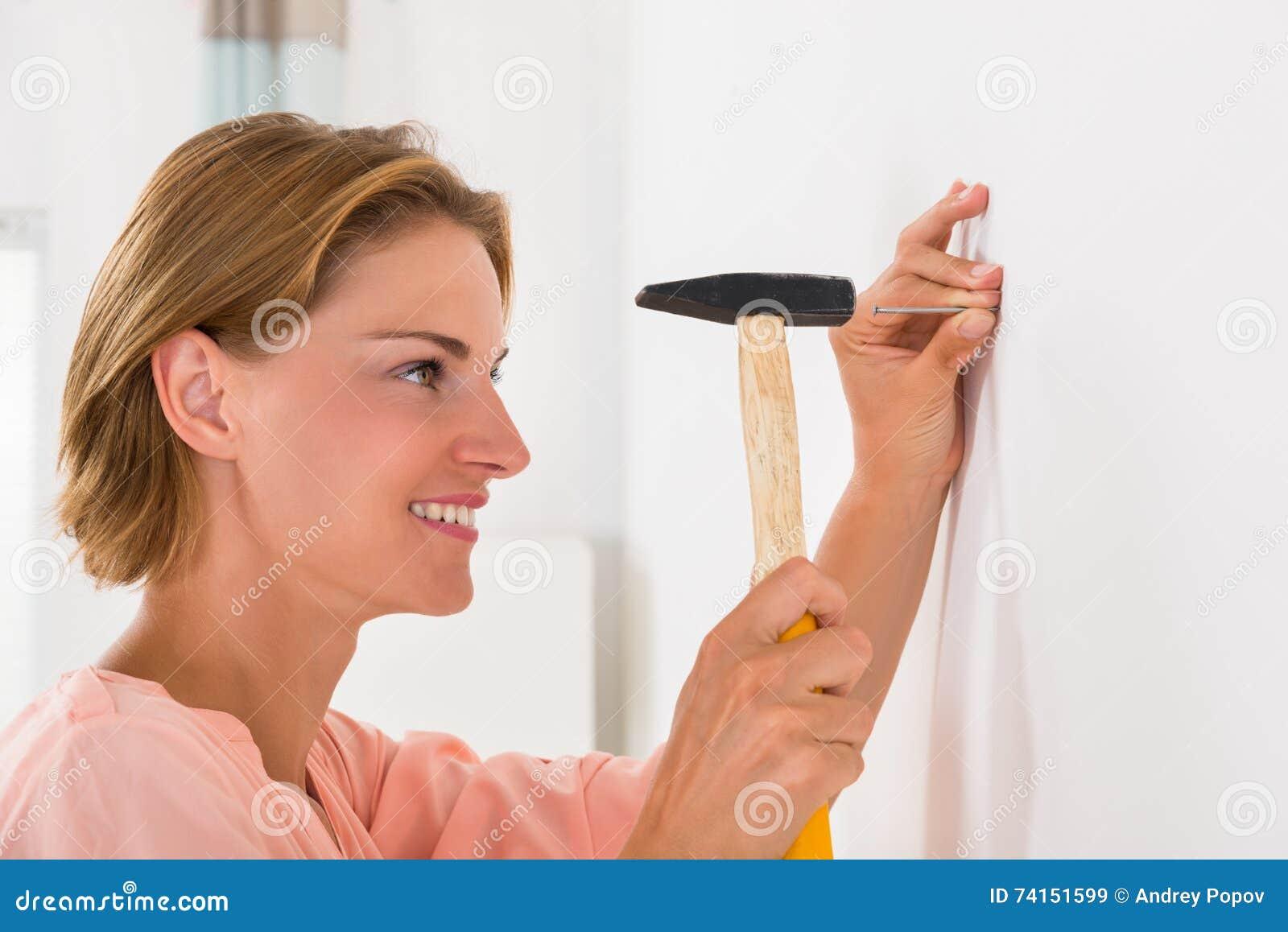 Молодая женщина ударяя ноготь в стене