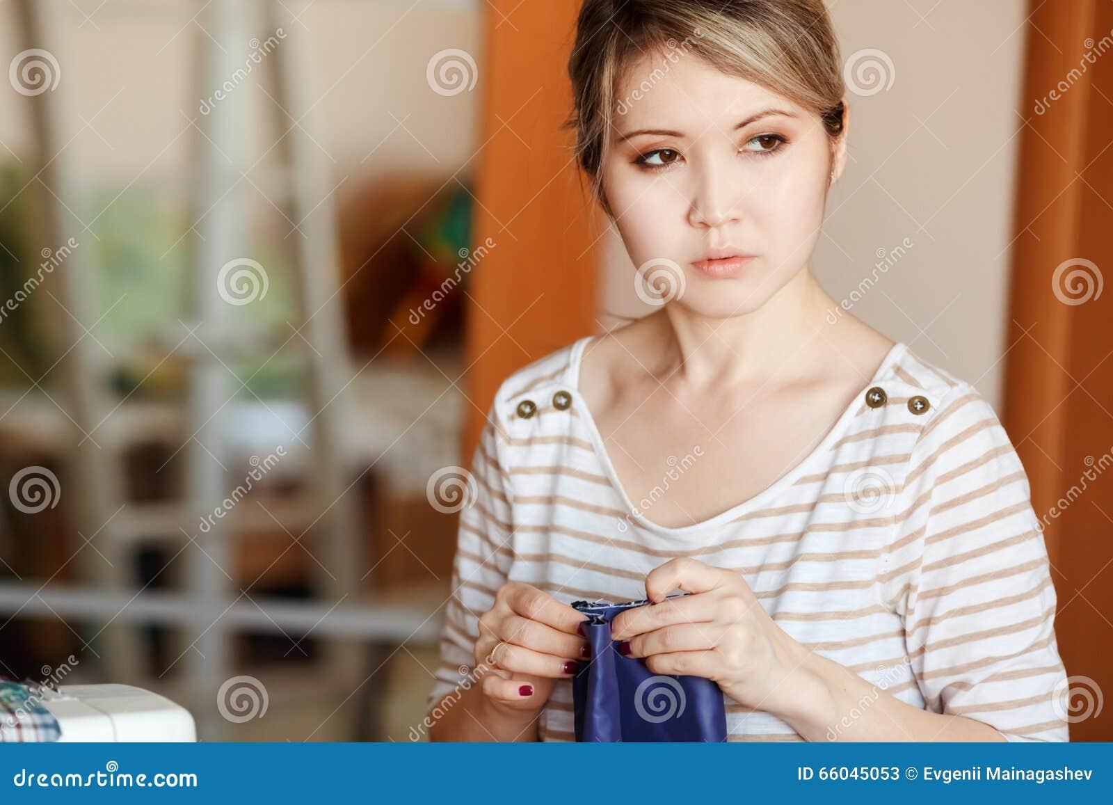 Молодая женщина шить дома, подшивающ голубую ткань, стоит и смотрит задумчиво к стороне скопируйте космос Создаваться модельера н