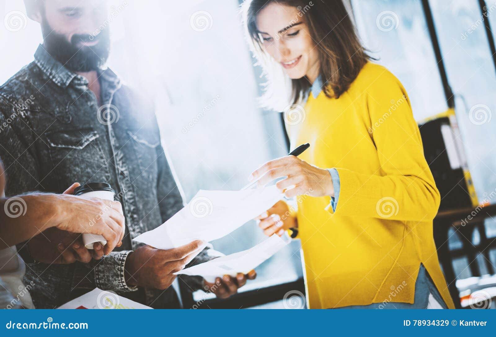 Молодая команда сотрудников делая большое обсуждение в солнечном офисе около окна Женщина подписывая бумаги горизонтально