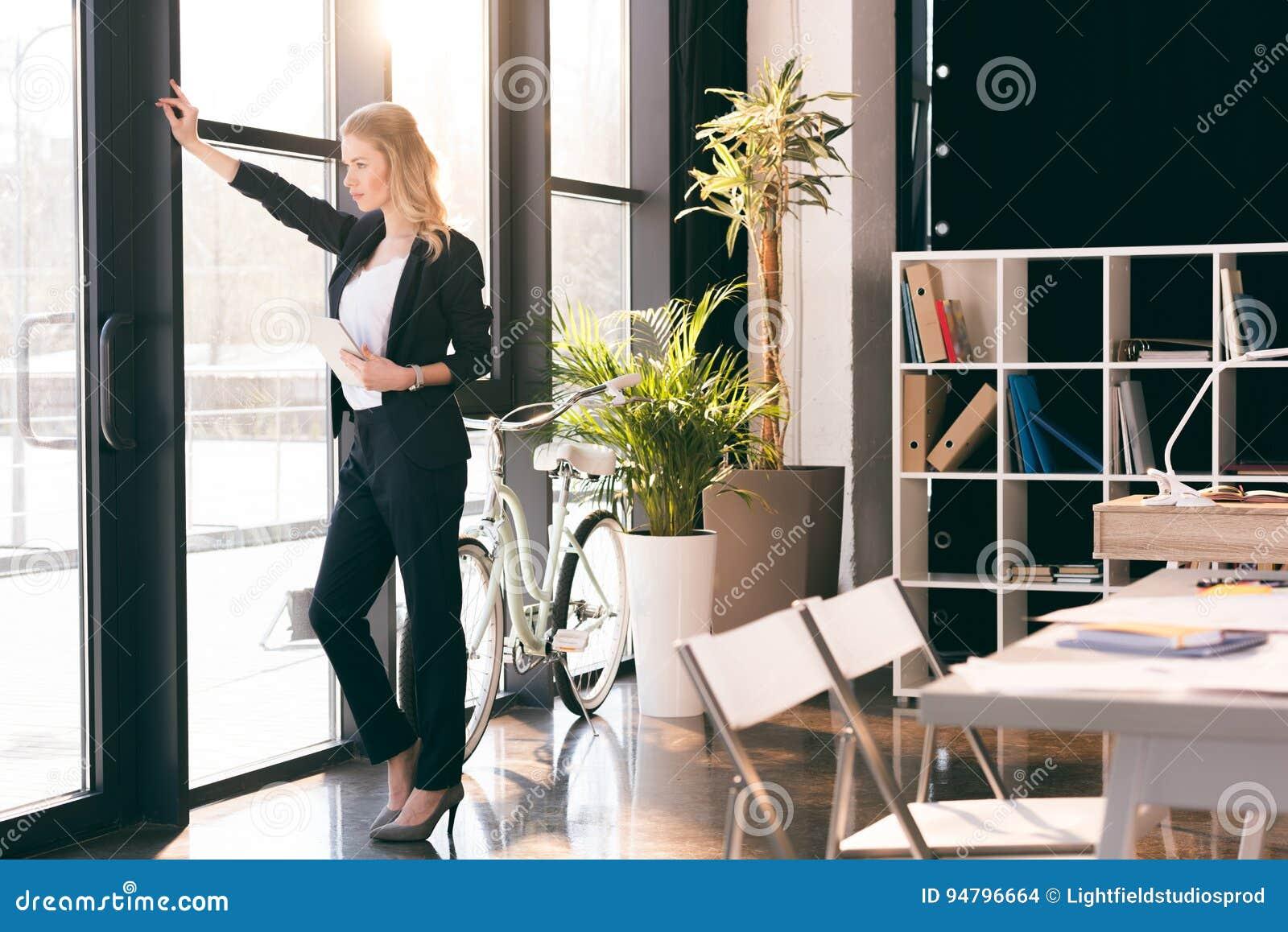Молодая коммерсантка держа цифровую таблетку и смотря окно в современном офисе