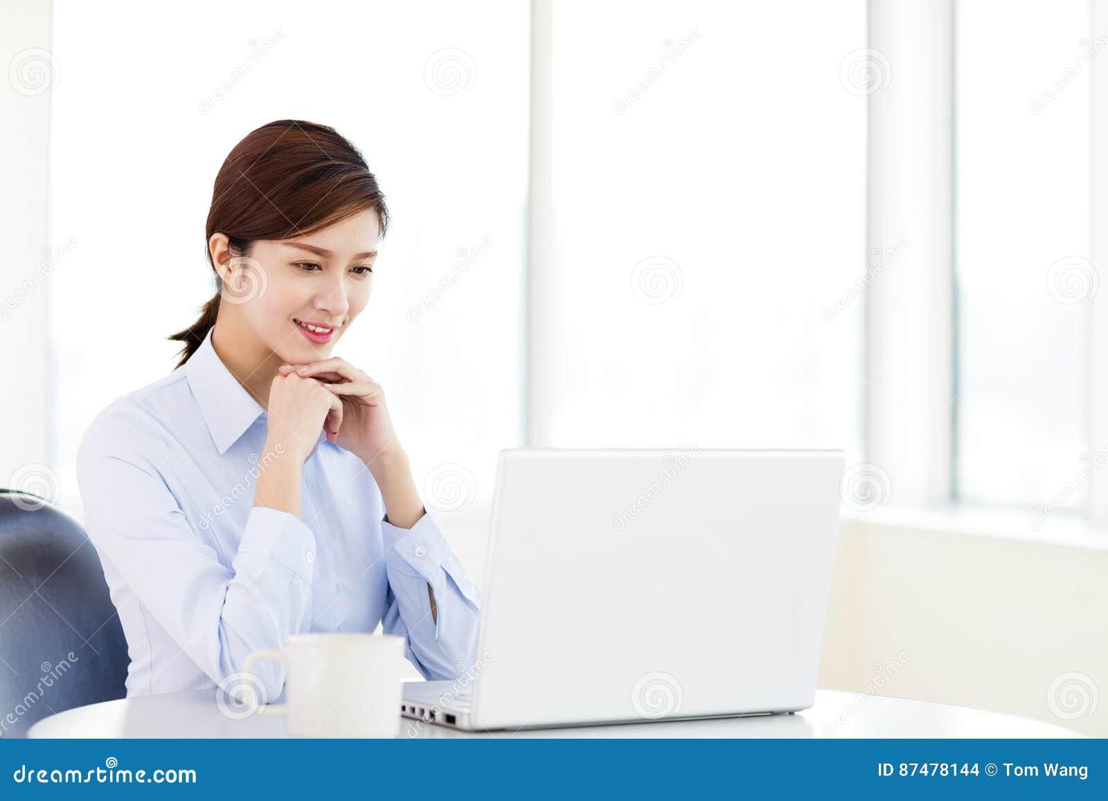 Молодая коммерсантка с компьтер-книжкой в офисе