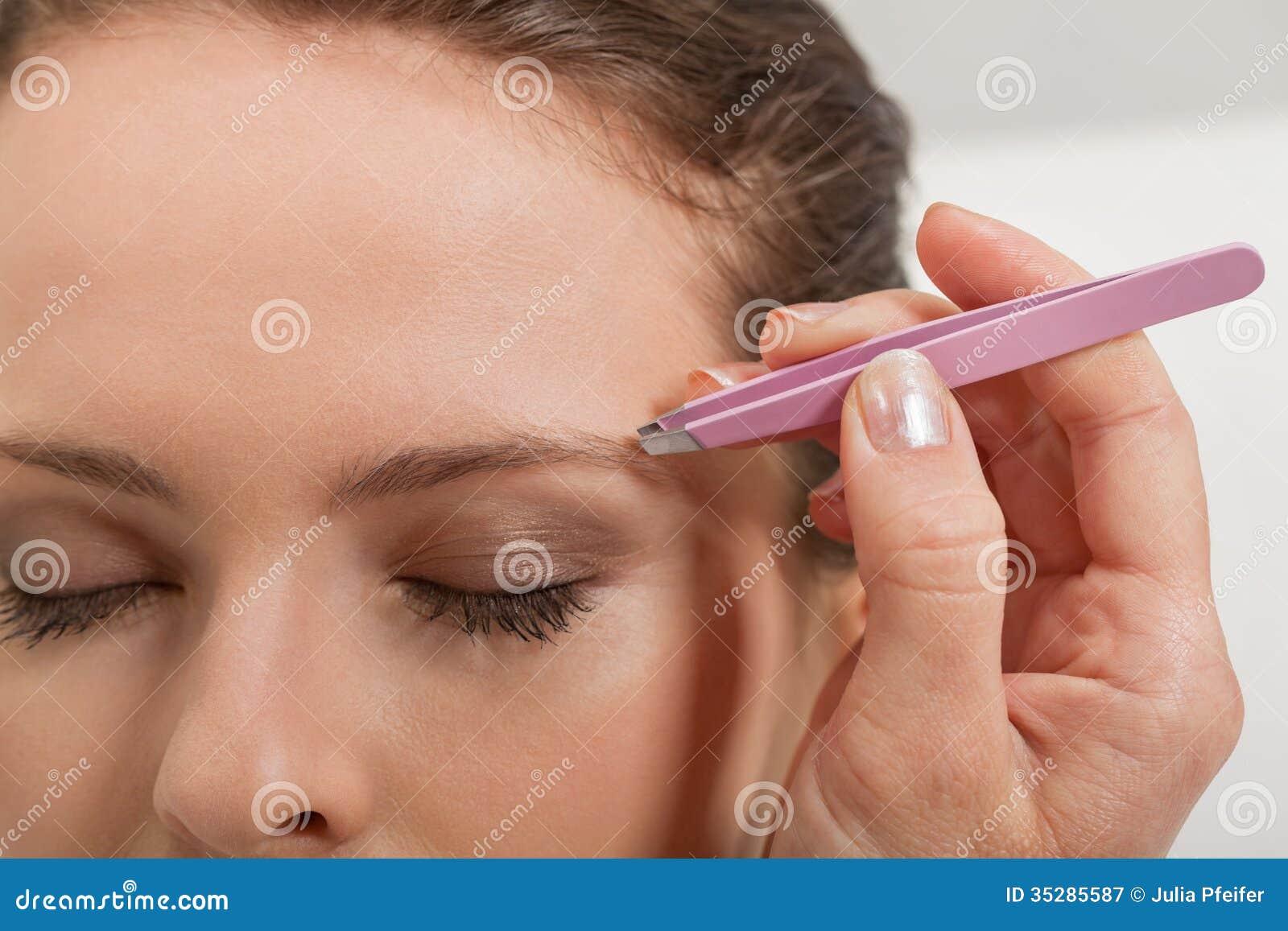 Молодая красивая бровь женщины общипывая щипчики наблюдает волосы