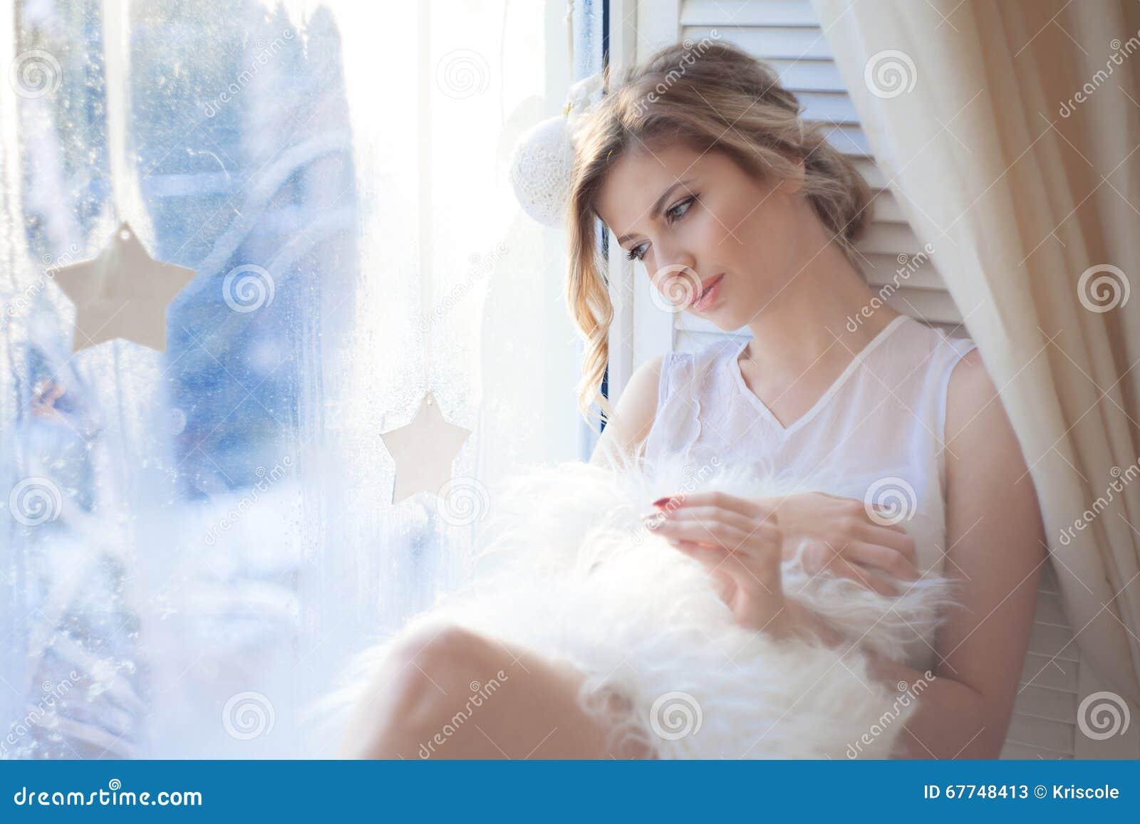 Молодая красивая девушка сидя на windowsill, смотря вне окно, свет утра, слепимость