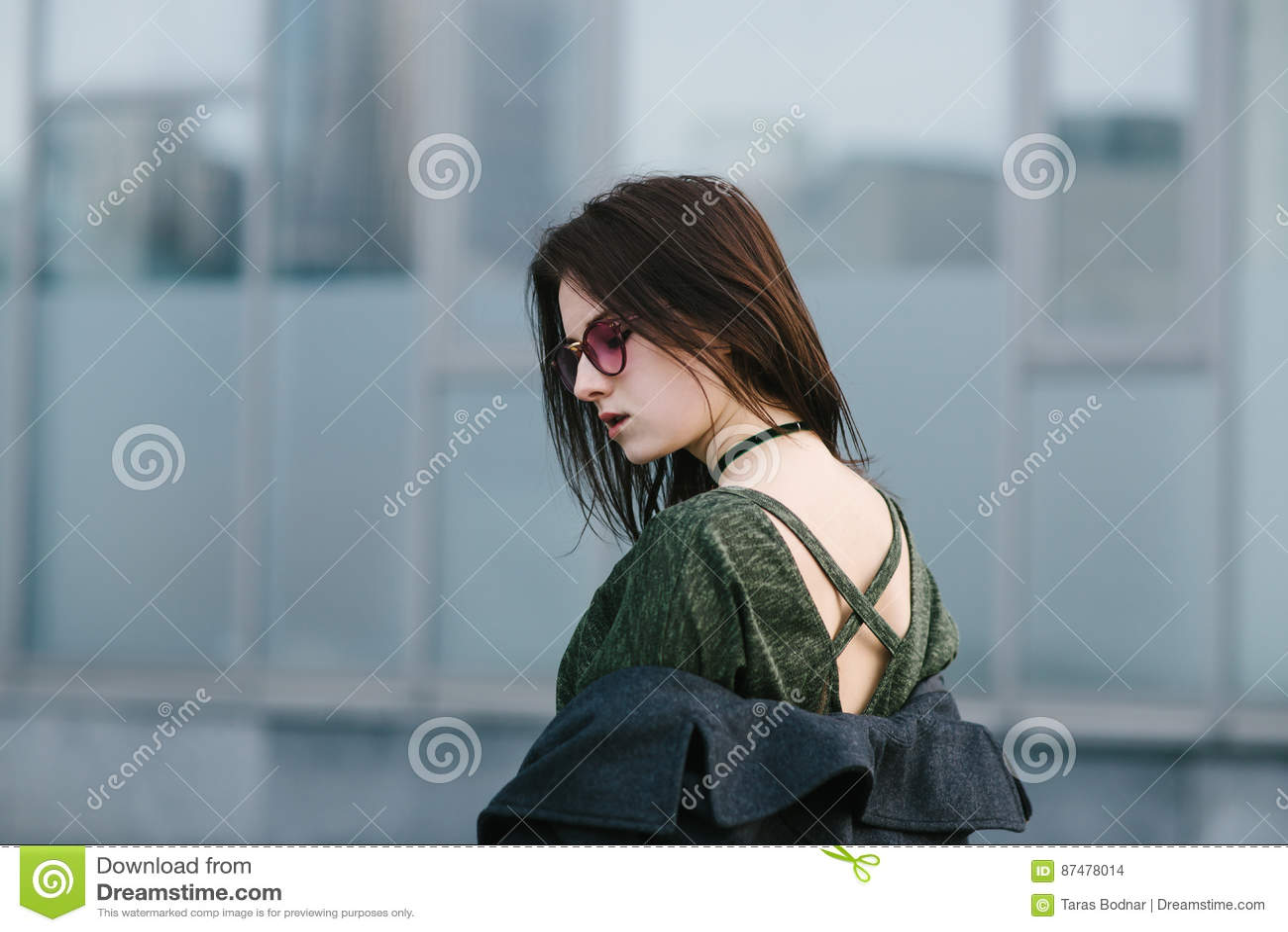 Молодая красивая женщина брюнет представляя на камере подвергая действию их задние части против фона современной архитектуры