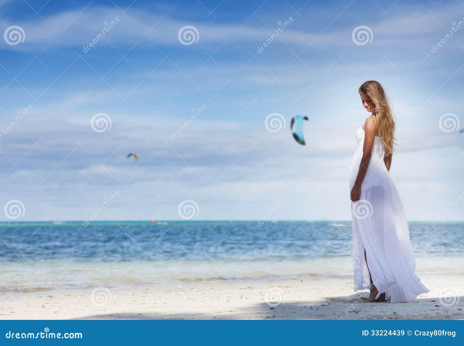 Молодая красивая женщина в платье свадьбы на тропическом пляже